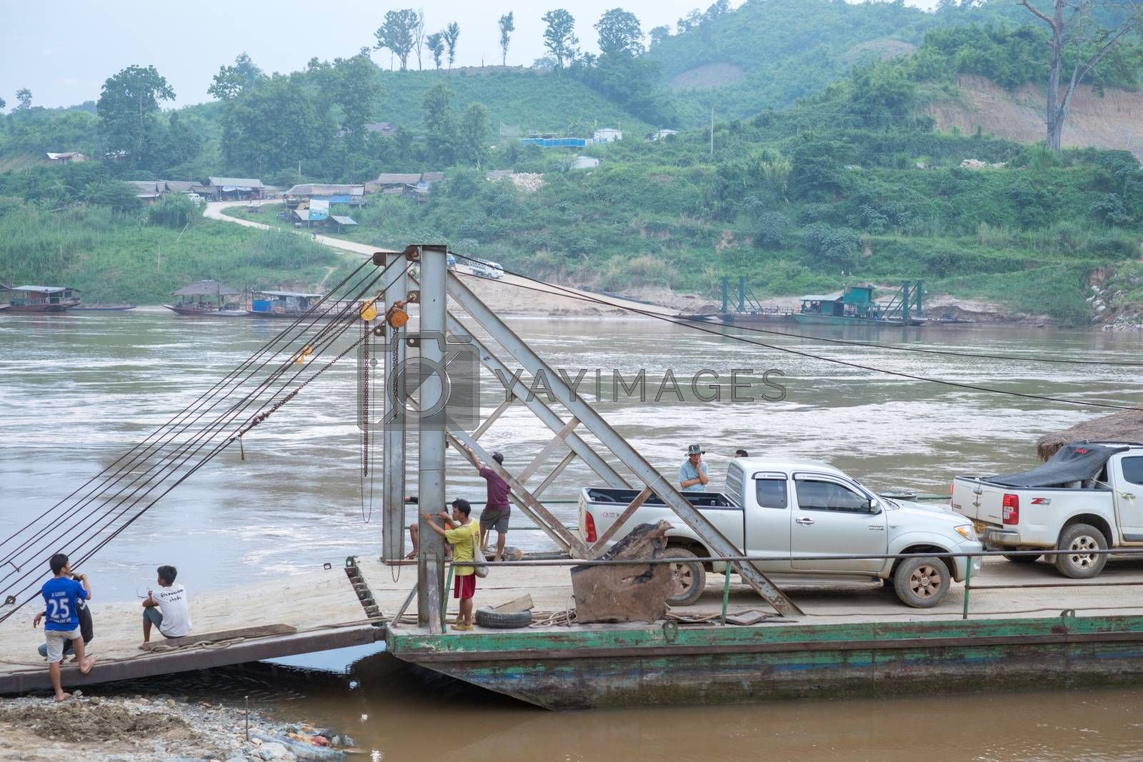 Unidentified ferry is carrying trucks across the Mekong River on June 10,2015 in Houay xai harbor, Bokeo , Laos pdr