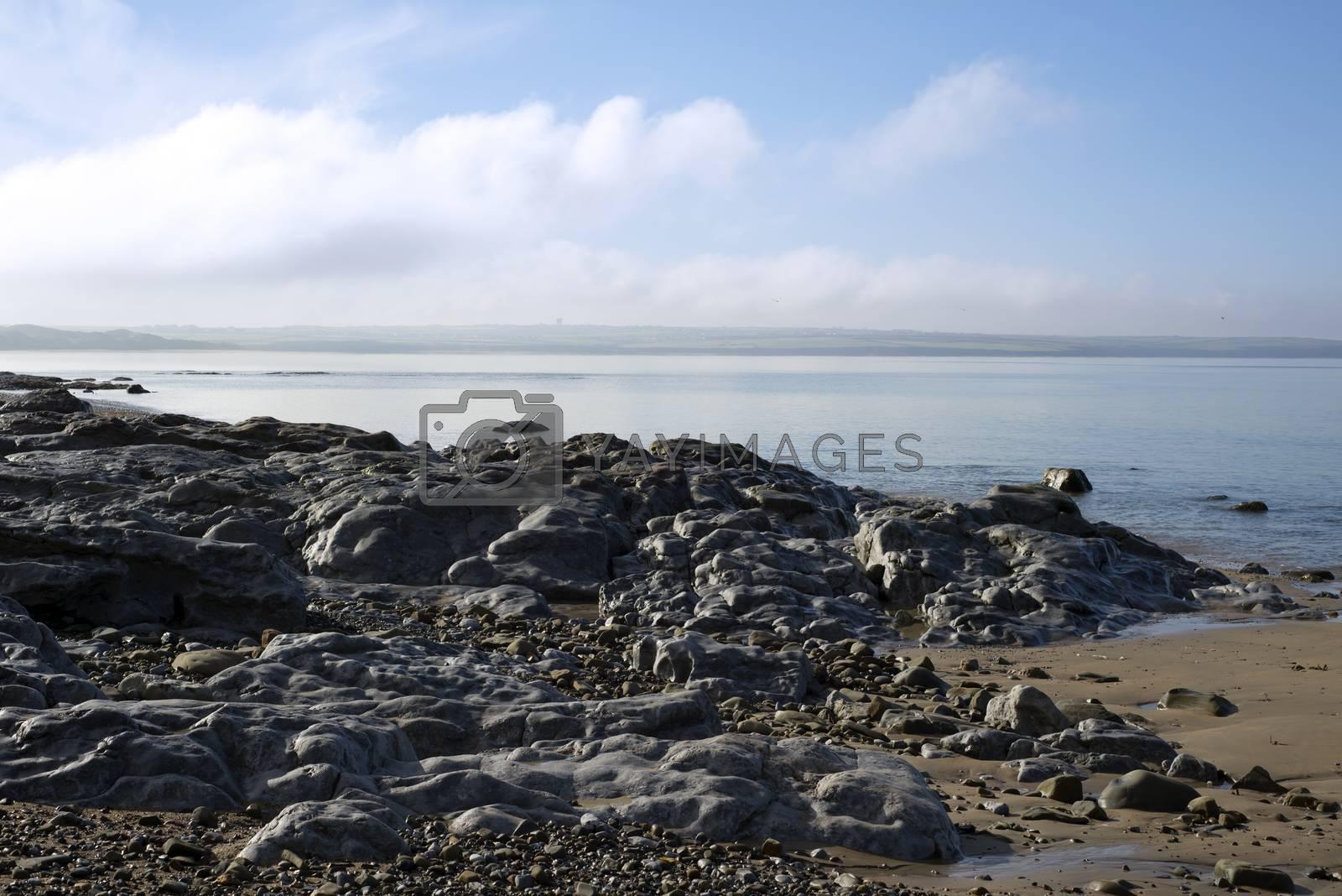 beautiful soft waves break on the black rocks at ballybunion beach in ireland