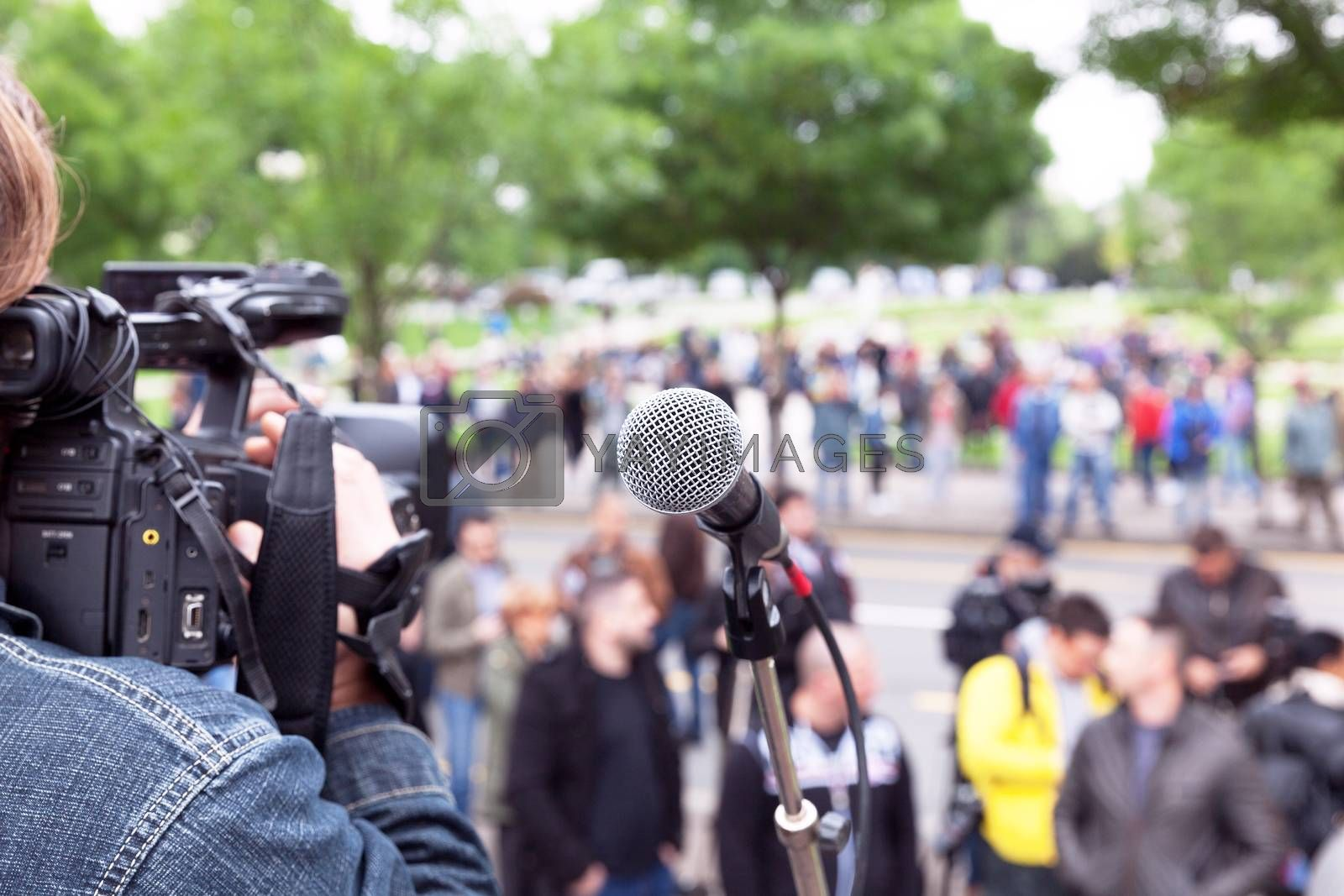 Microphone in focus, camera operator shooting blurred crowd