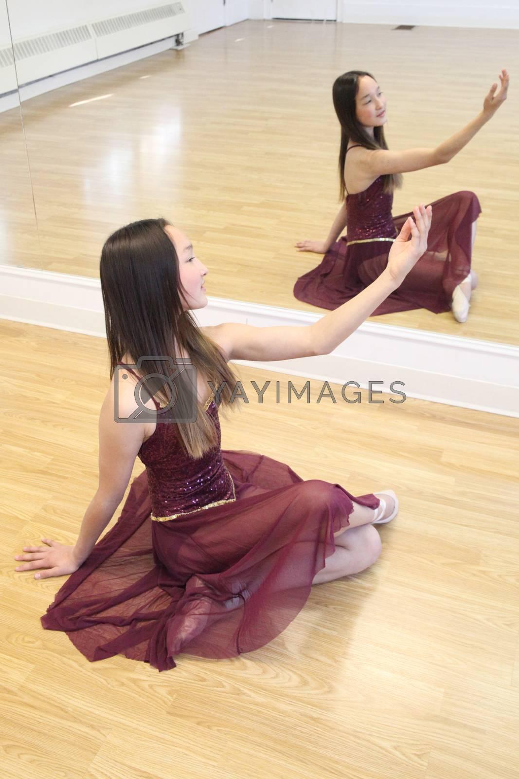 Beautiful brunette teen dancer in a burgundy costume
