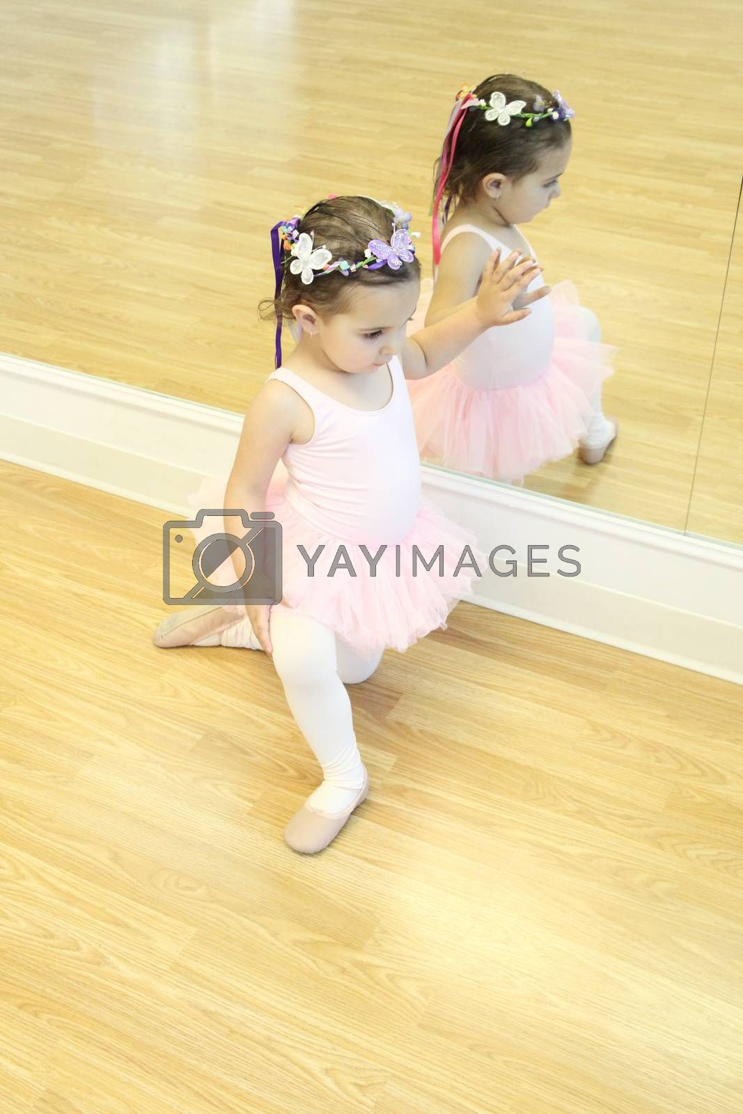 Little ballet girl sitting in front of a mirror