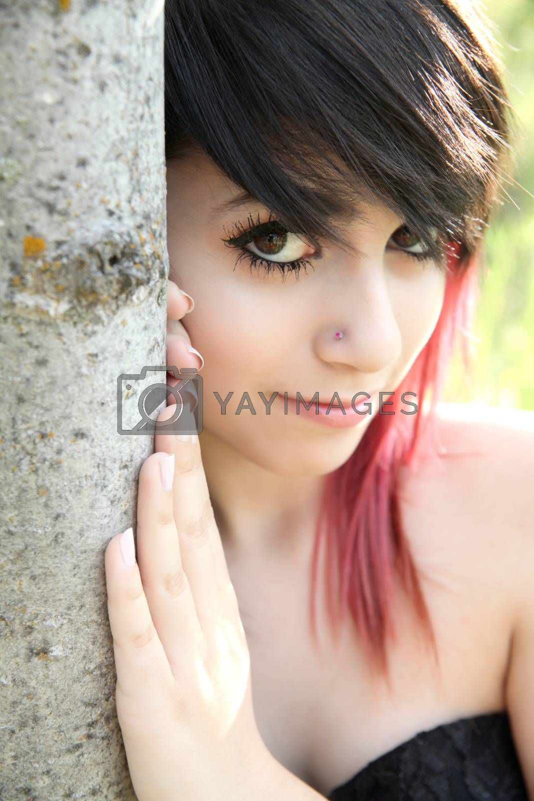 Beautiful brunette girl leaning against the trunk of a tree