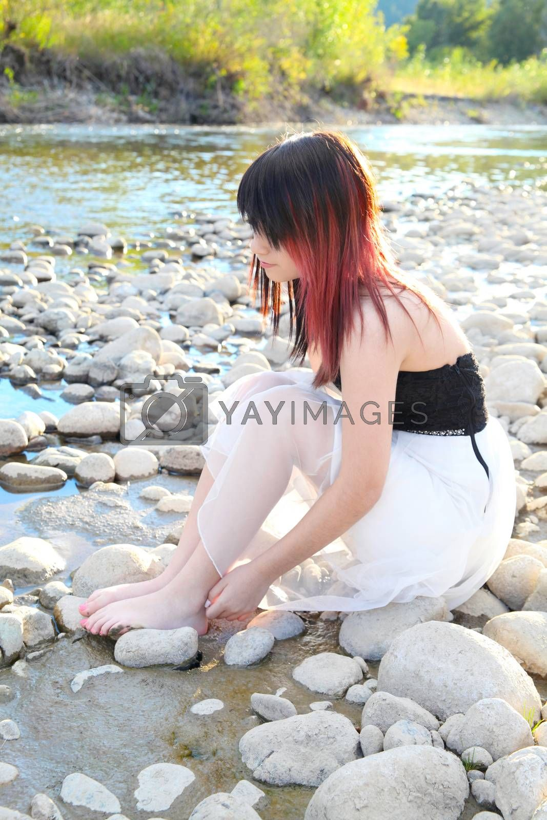 Beautiful brunette girl sitting by the river