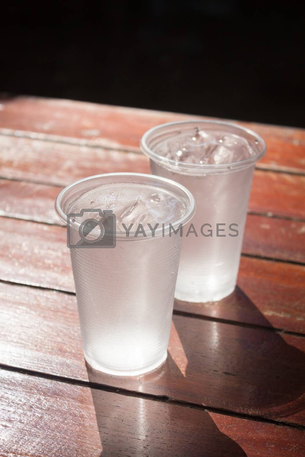 Glass of water on wooden table by punsayaporn