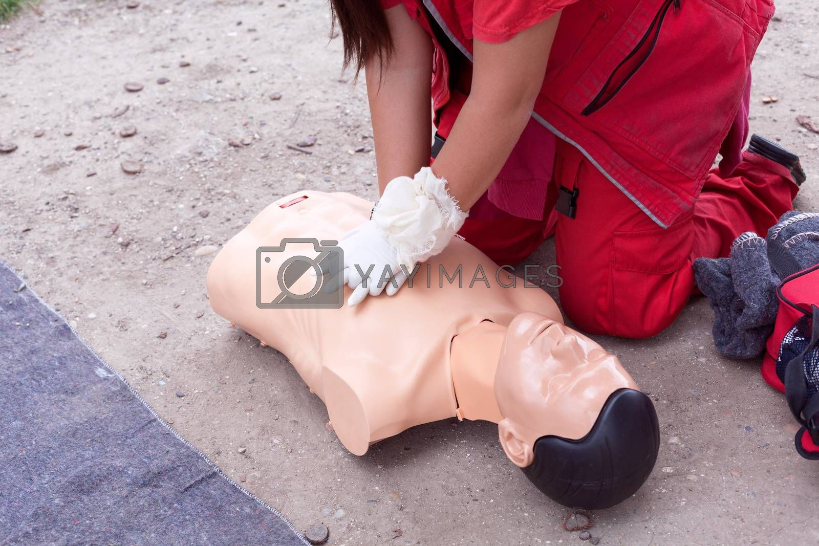 Female instructor showing cardiopulmonary resuscitation - CPR on training doll. First aid training.