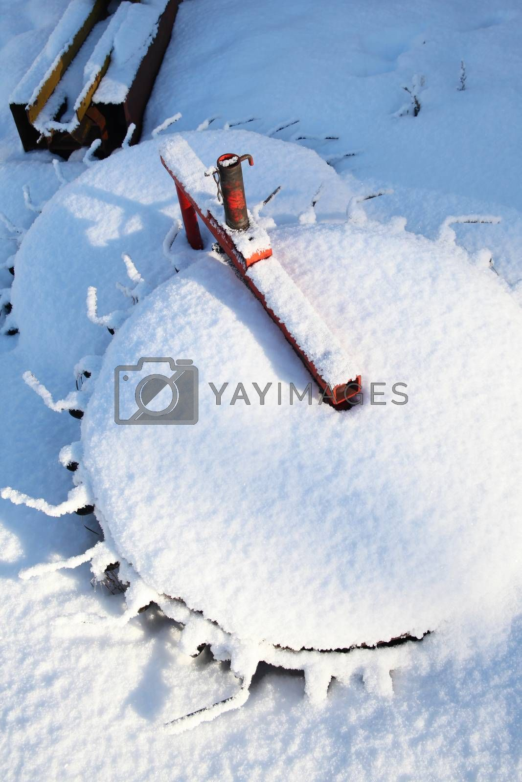 Snow covered farm equipment on a sunny day