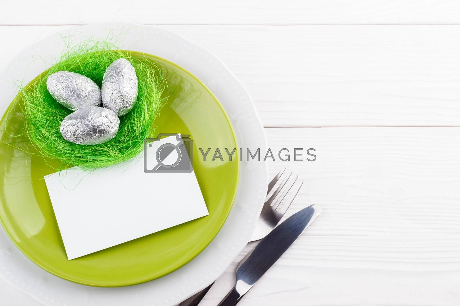 Spring easter table setting with silverware chocolate eggs in a nest, copy space