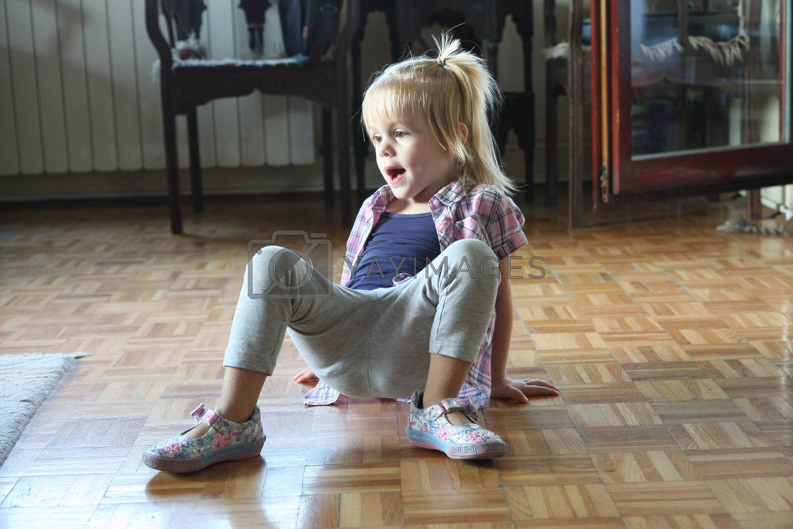 Cute young girl playing on the floor