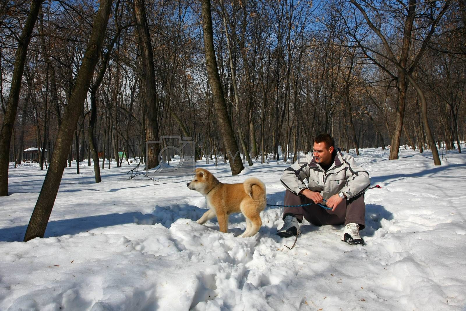 Young man enjoying on the snow  with its Akita Inu puppy