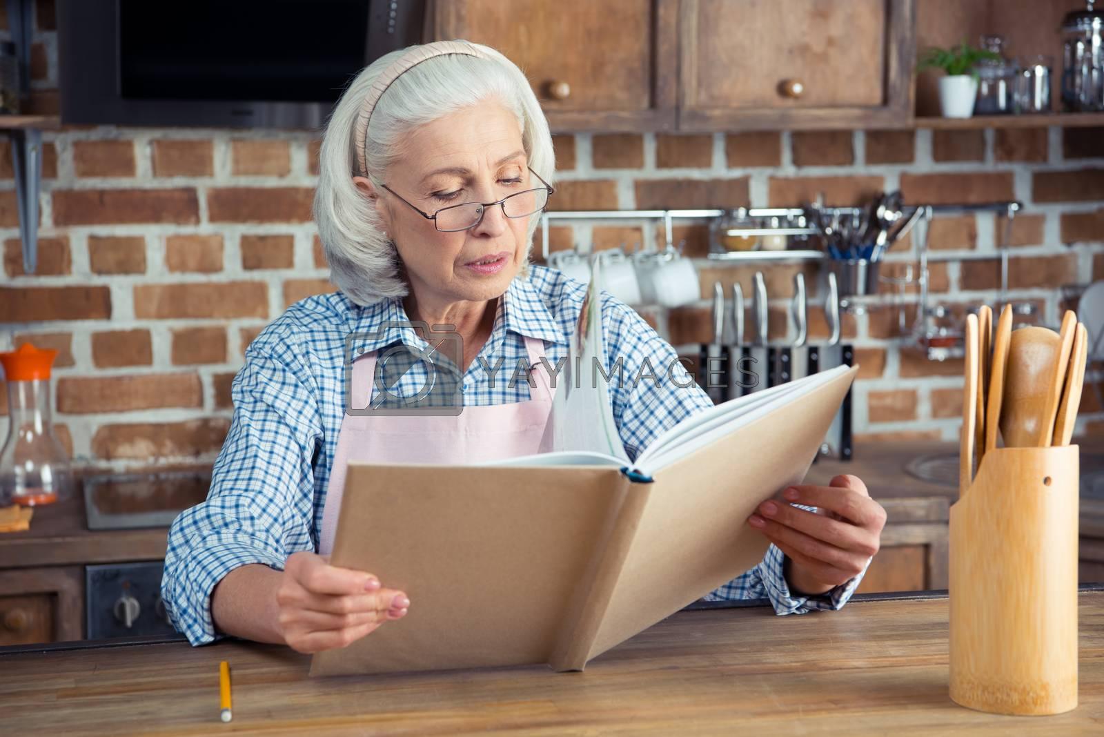 Senior woman in eyeglasses reading cookbook in kitchen