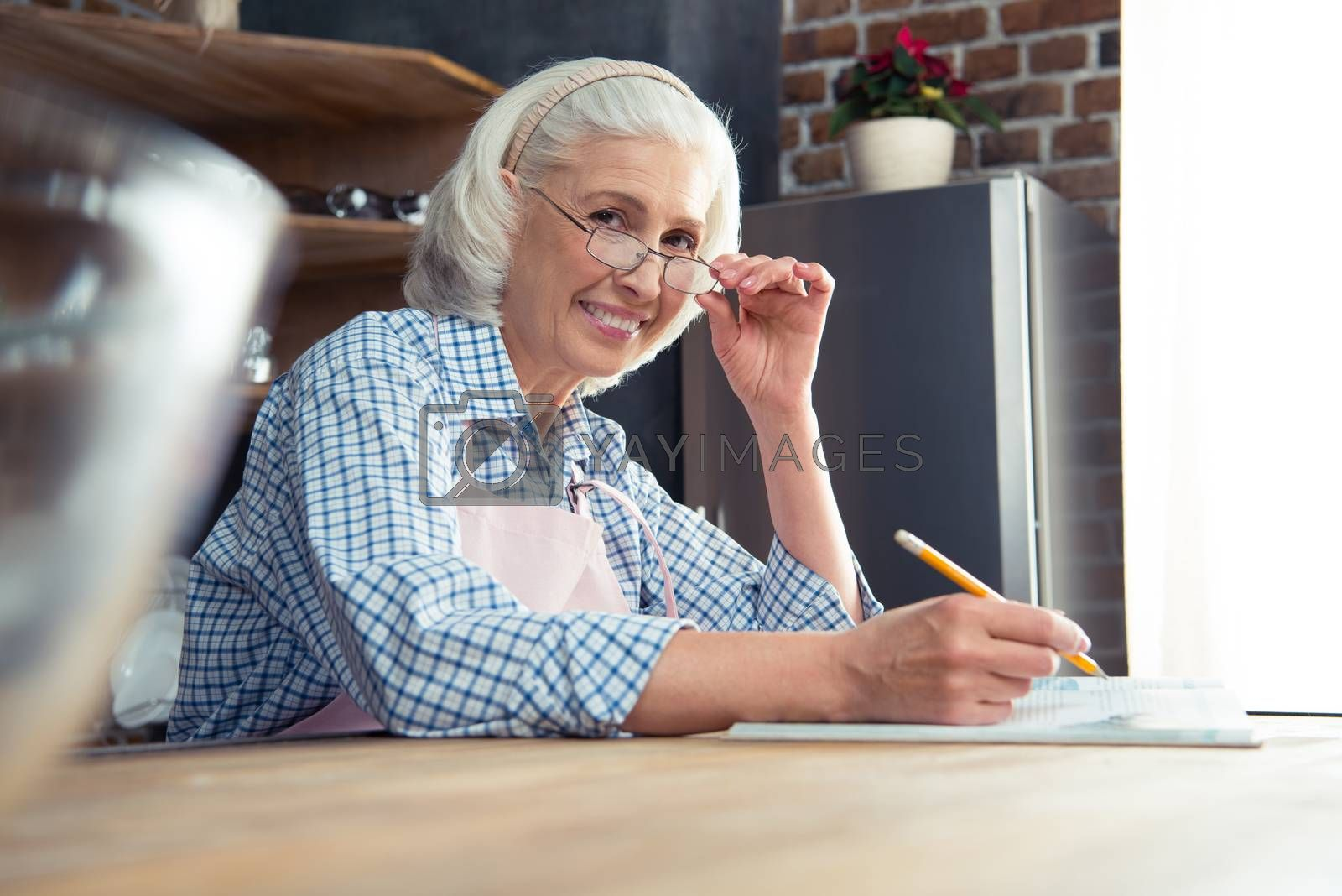Smiling senior woman with cookbook looking at camera