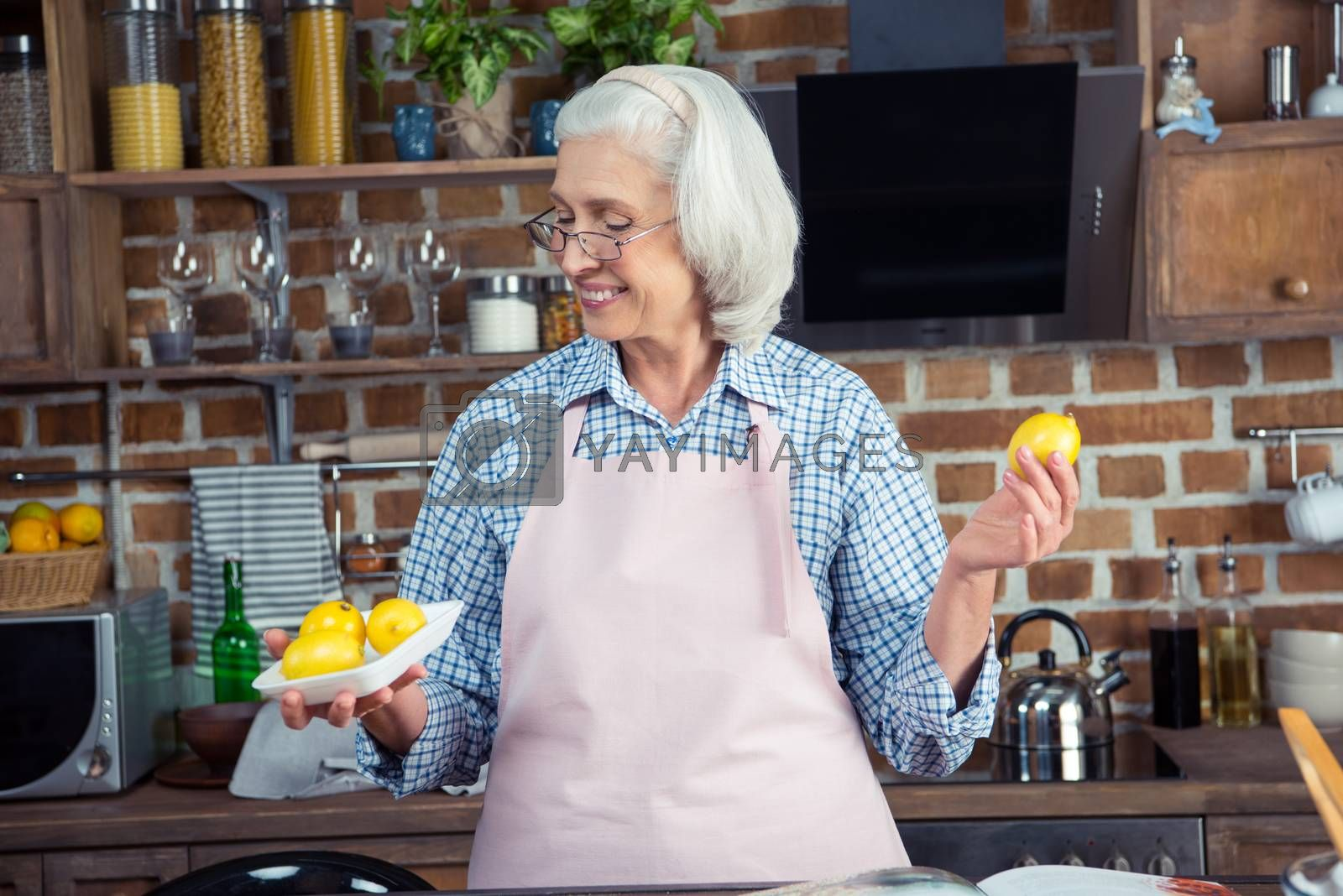 Smiling senior woman in eyeglasses and apron looking at lemons in kitchen