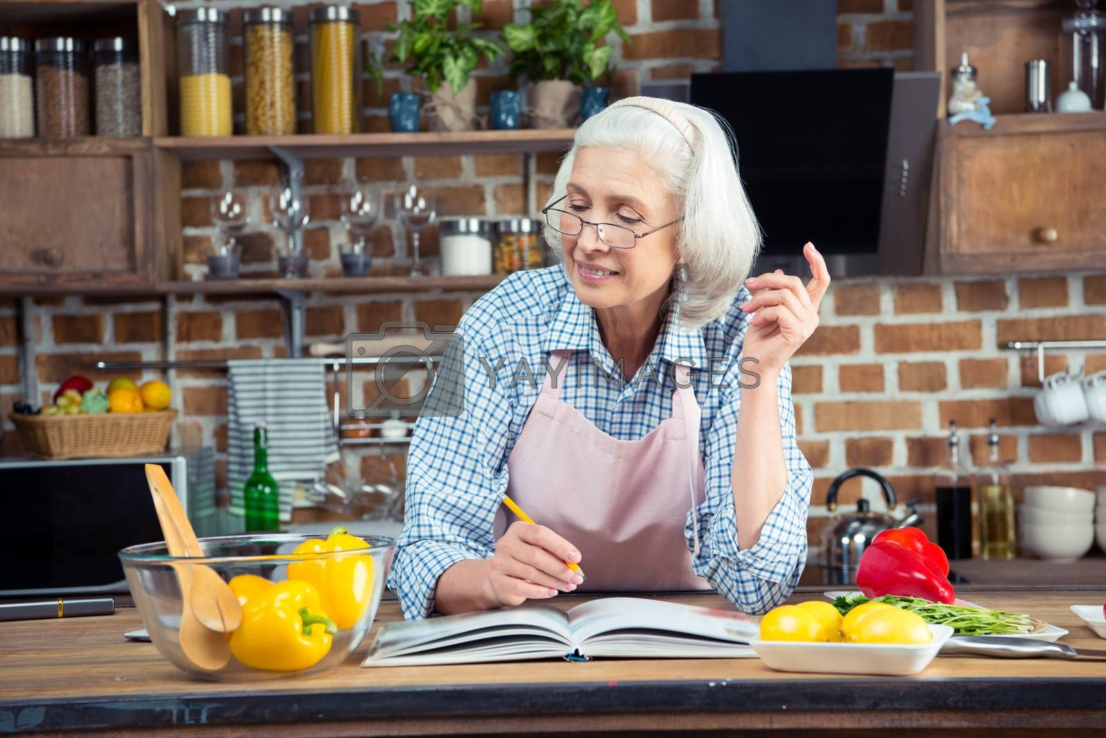Smiling senior woman writing in cookbook with pencil and looking at ingredients