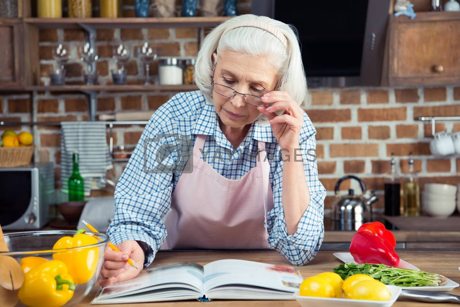Serious senior woman looking in cookbook while sitting in kitchen