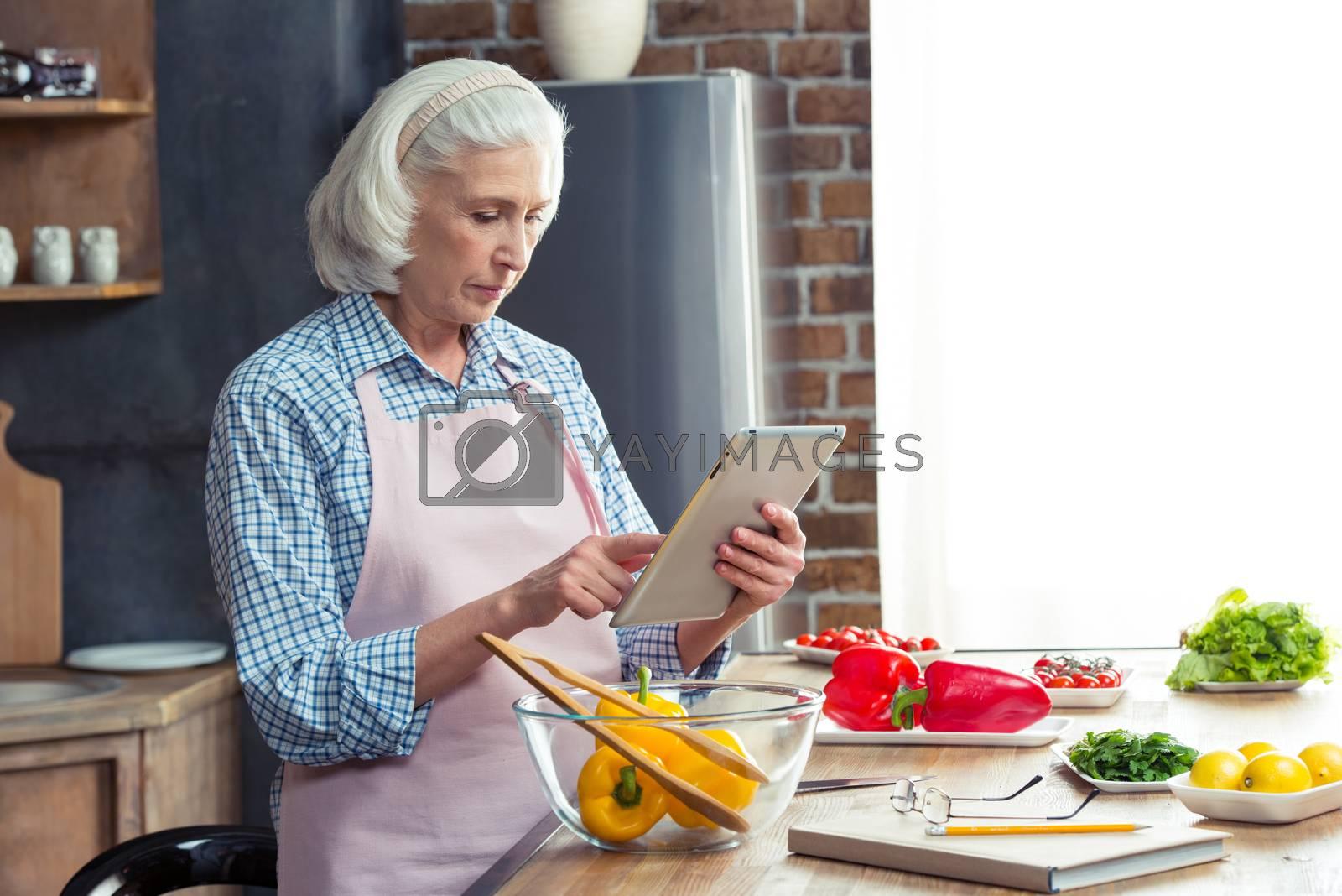 Senior woman using digital tablet in kitchen while preparing vegetable salad