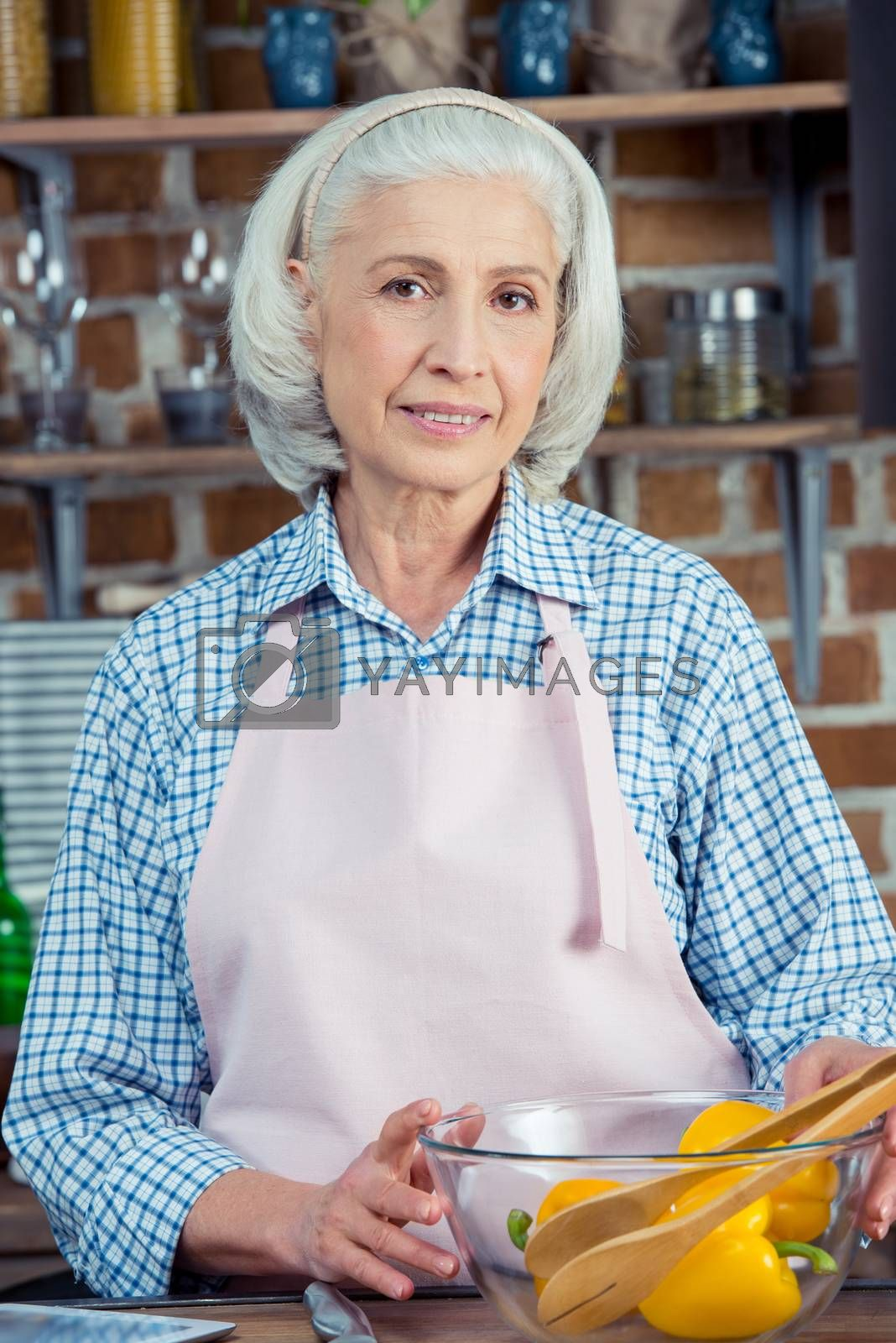 Attractive senior woman in apron smiling at camera in kitchen