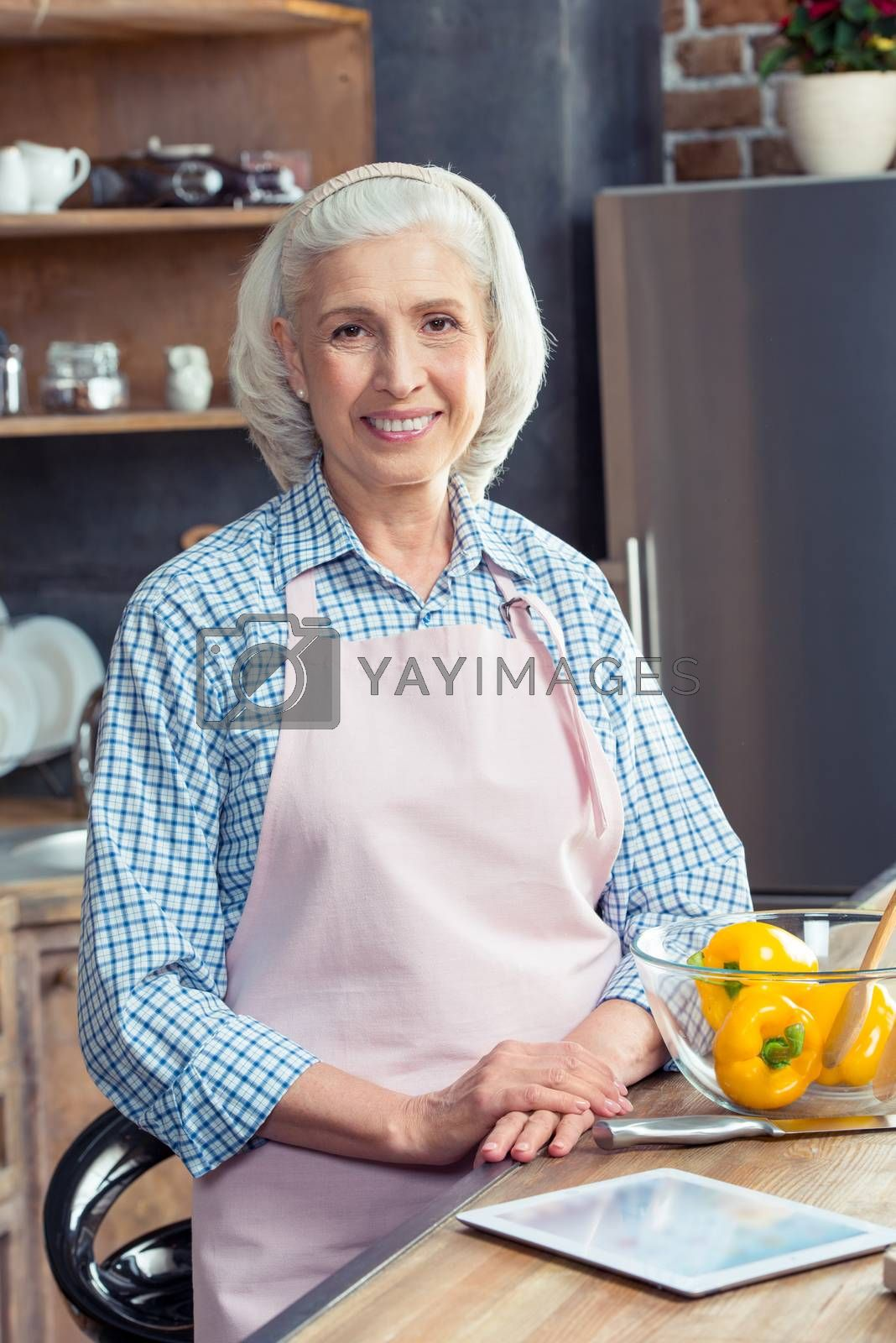 Senior woman in apron smiling at camera in kitchen