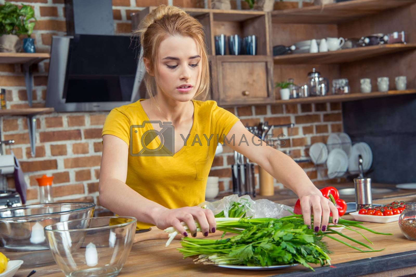 Attractive young woman holding green onions in kitchen
