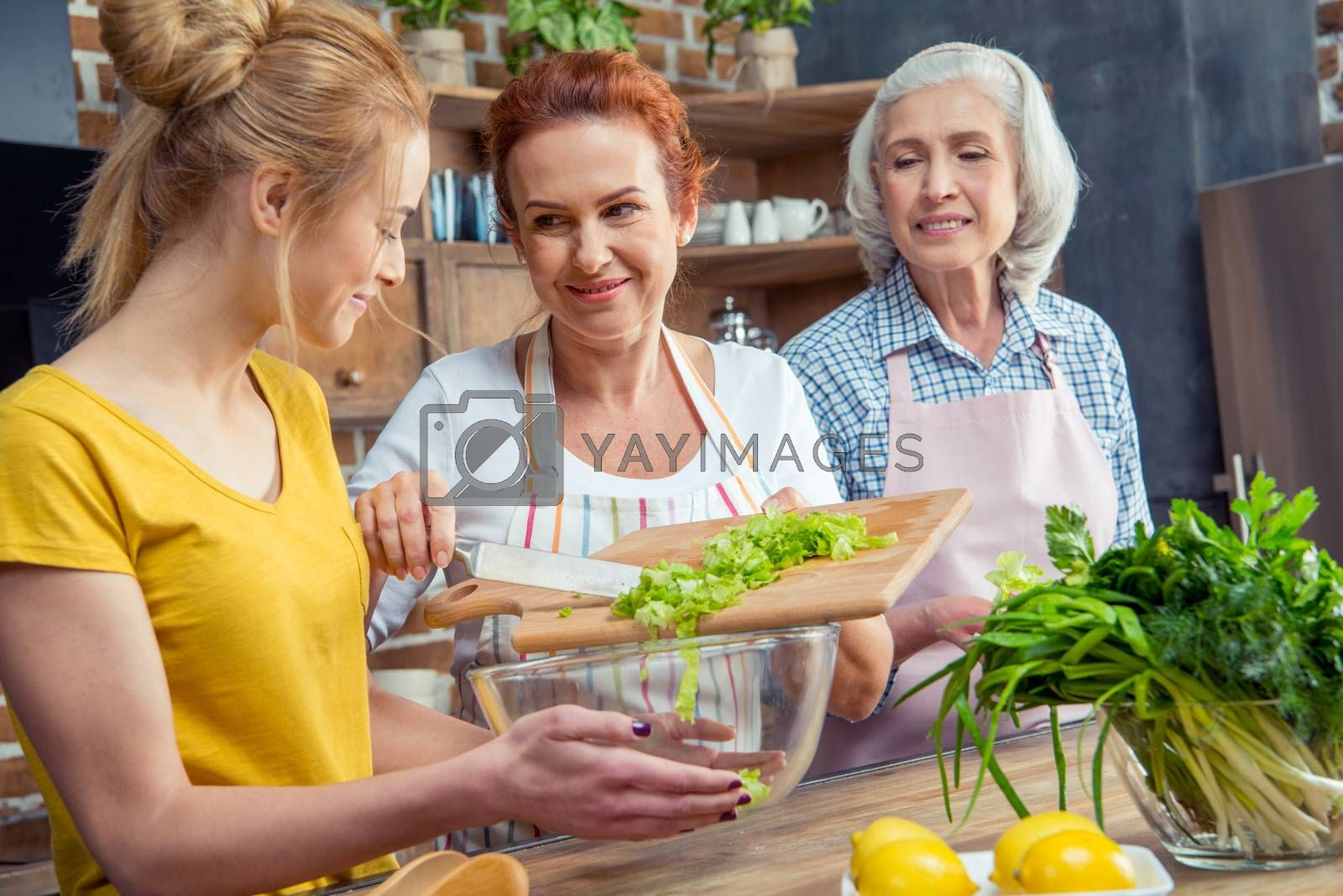Happy three-generation family cooking together in kitchen