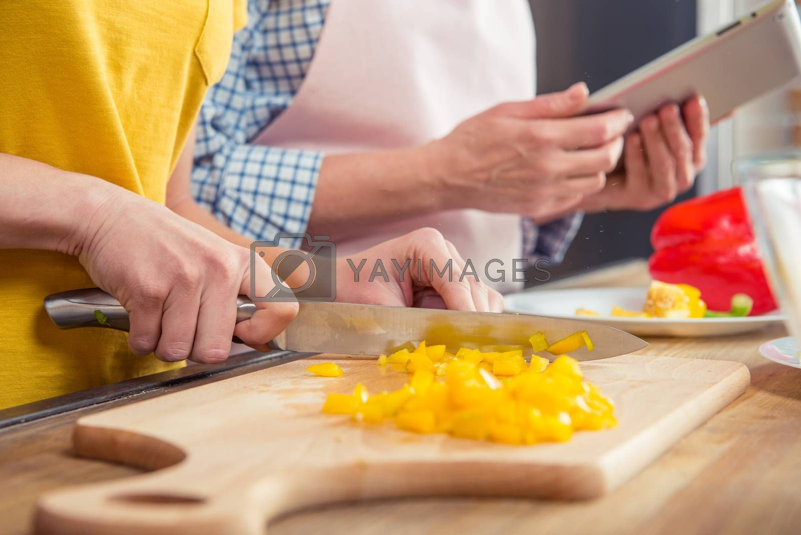 Close-up partial view of woman cutting pepper on cutting board