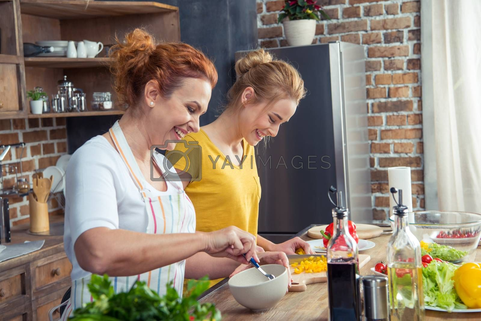 Smiling mother and daughter cooking together in kitchen