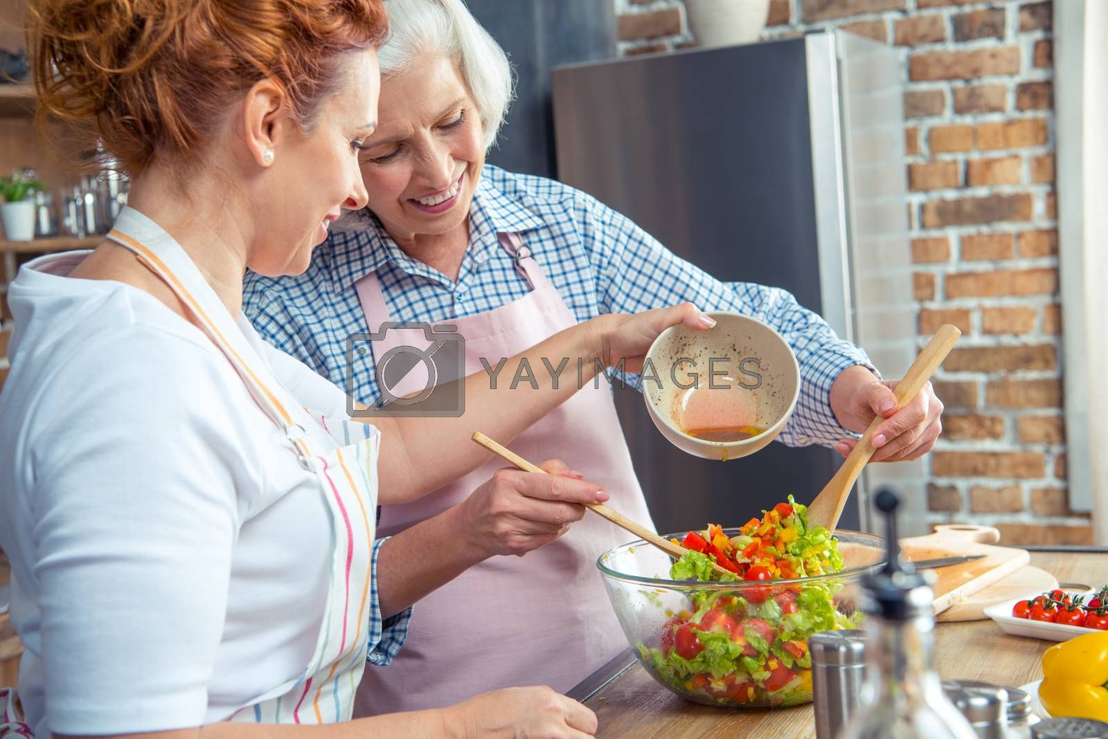 Two smiling women cooking vegetable salad together