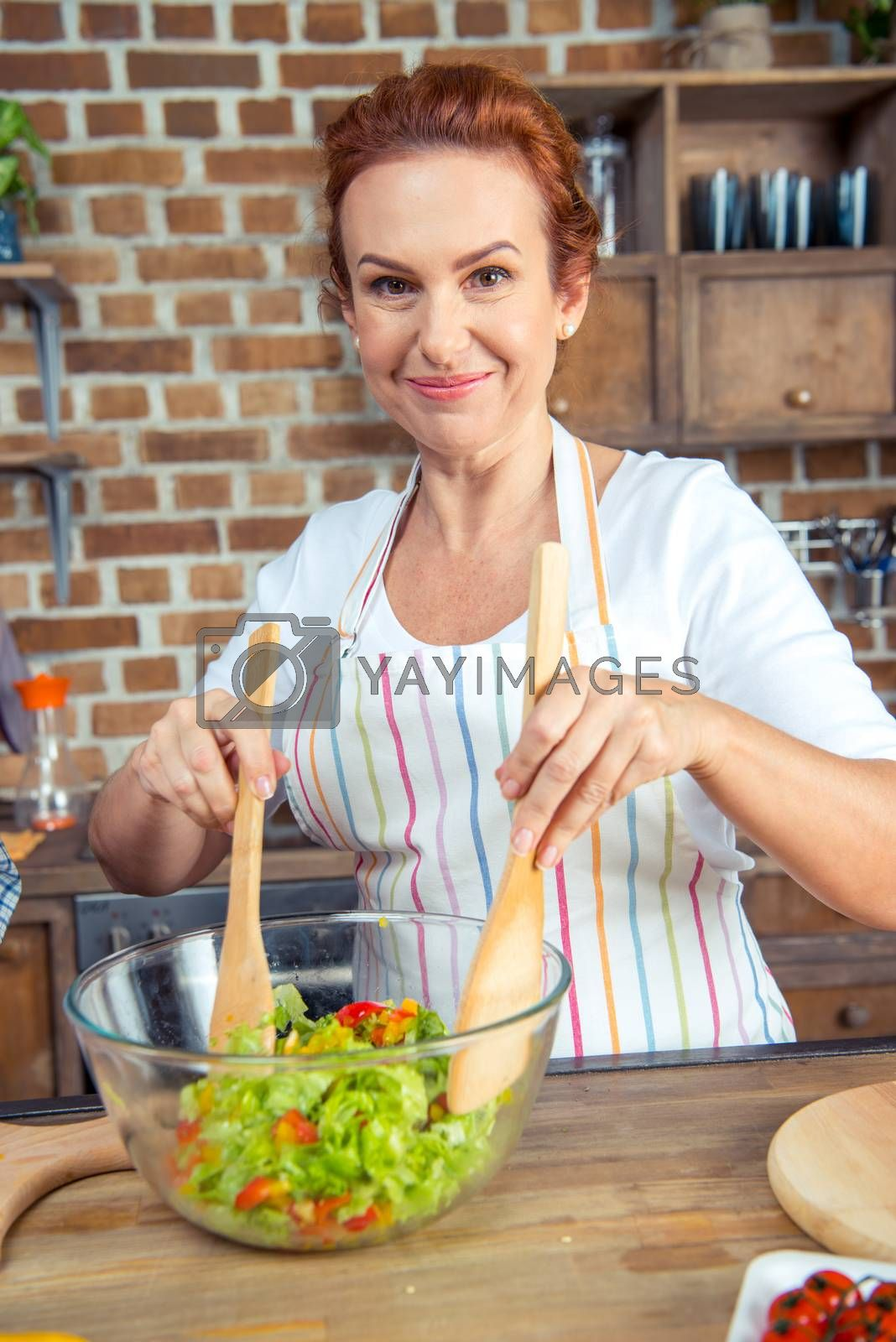 Smiling woman in apron mixing fresh vegetable salad in kitchen