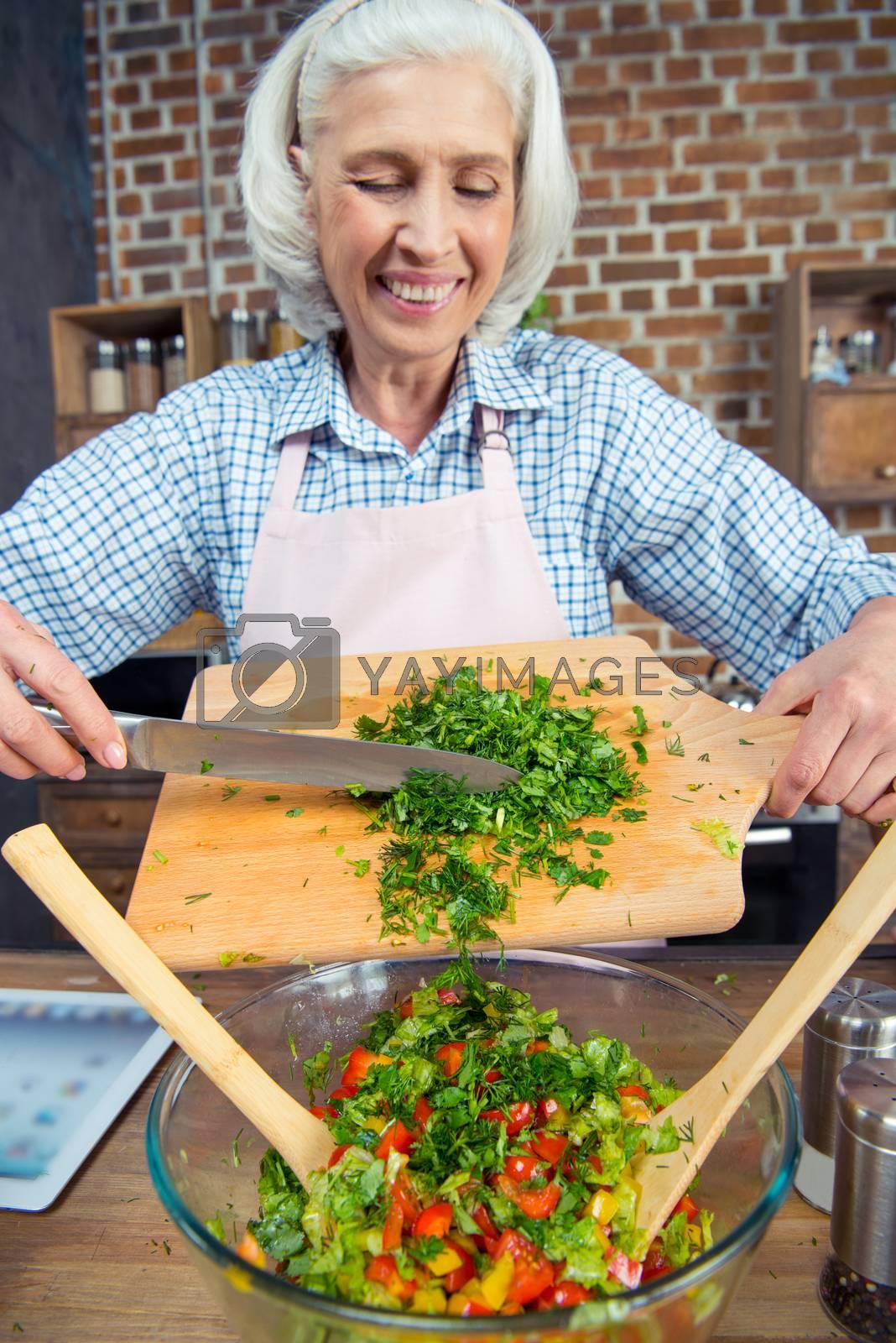 Smiling senior woman cutting salad greens