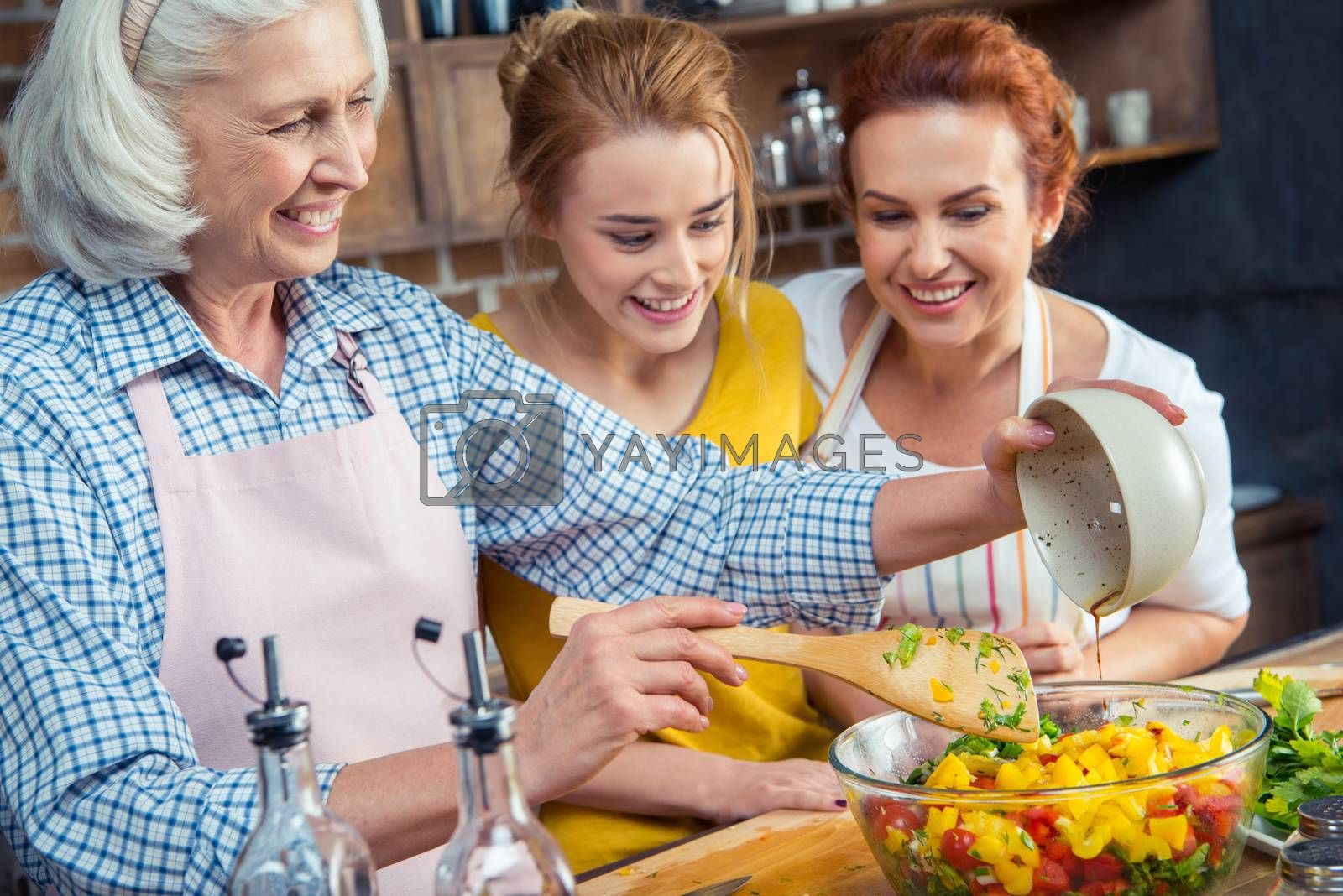 Happy three-generation family cooking vegetable salad together in kitchen