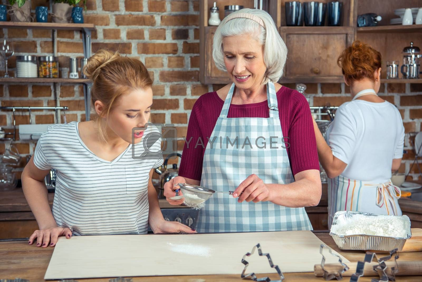 Grandmother and granddaughter sifting flour for cookies in kitchen
