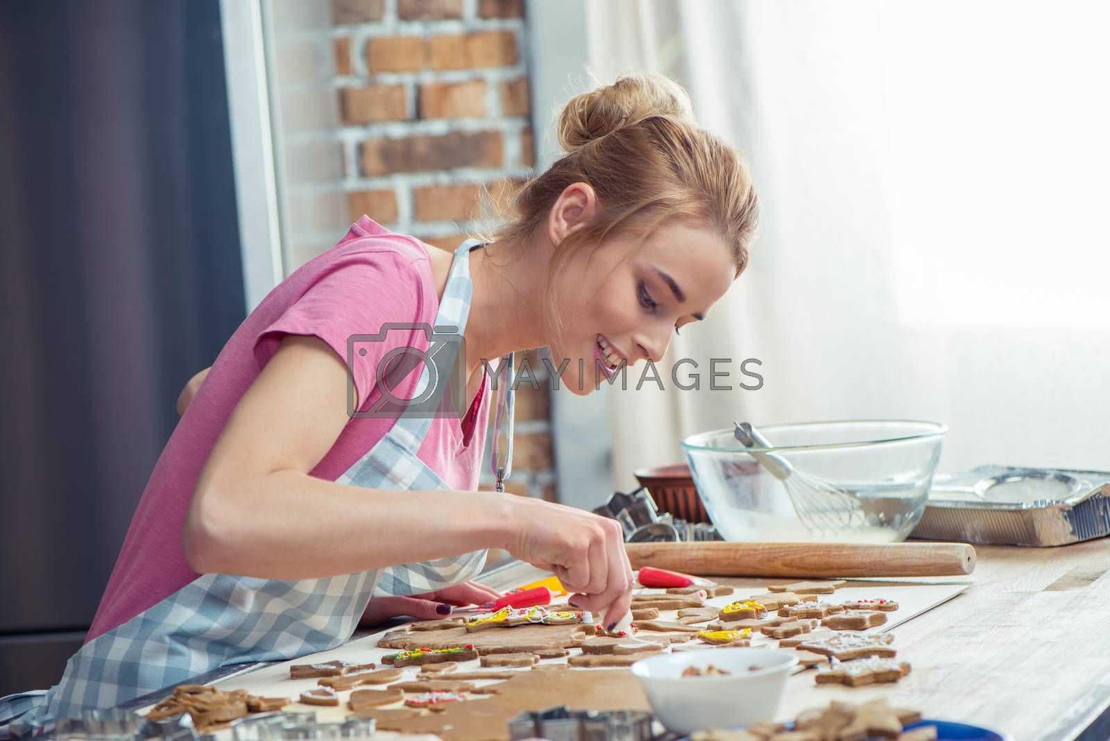 Teenage girl wearing apron and icing Christmas cookies