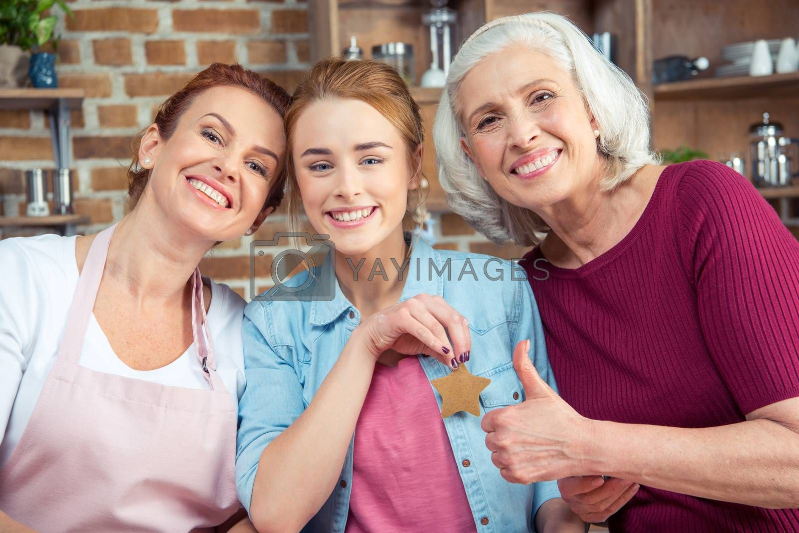 Happy family of three generations smiling and looking at camera. Senior woman showing thumb up