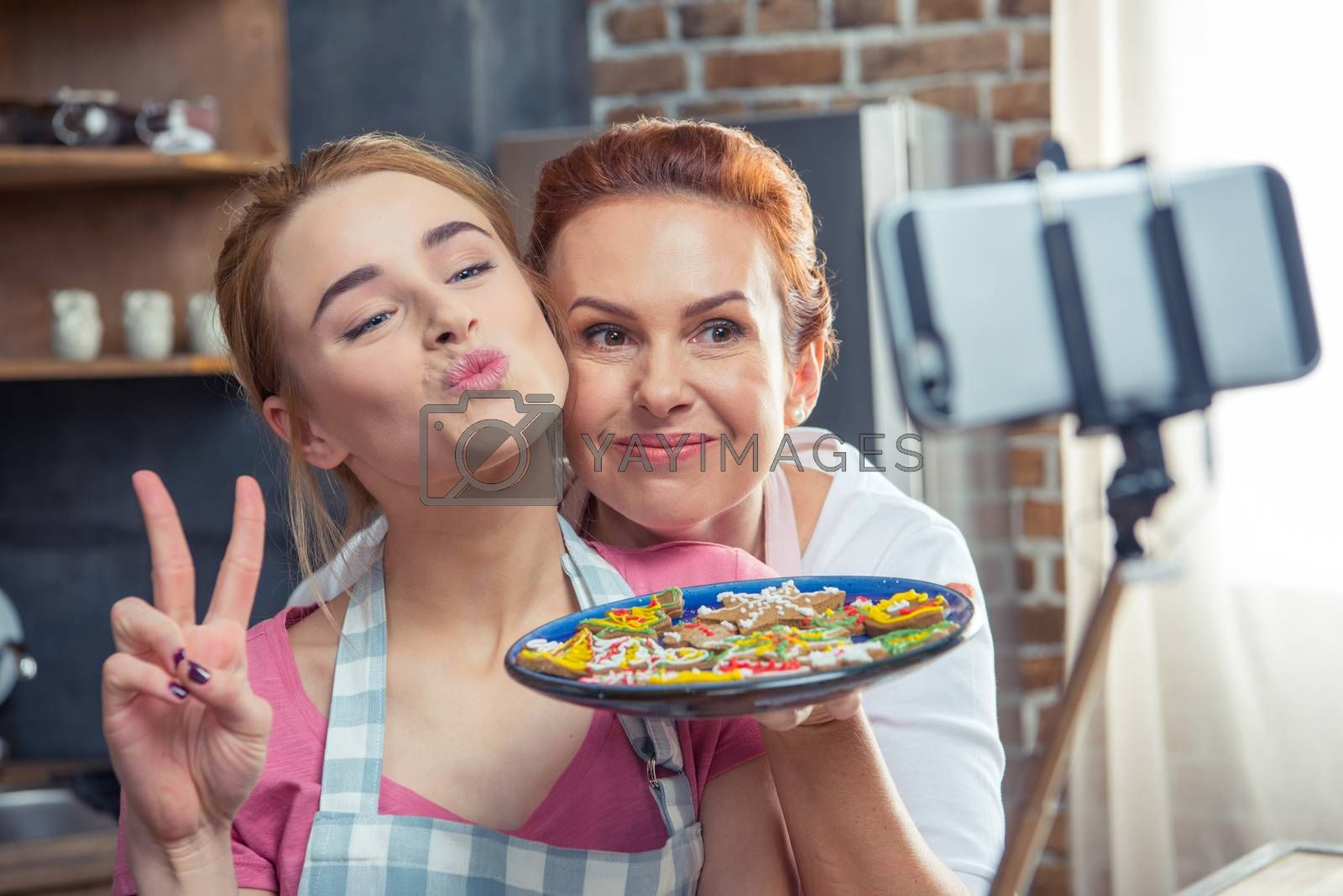 Mother and daughter making selfie holding plate with Christmas cookies