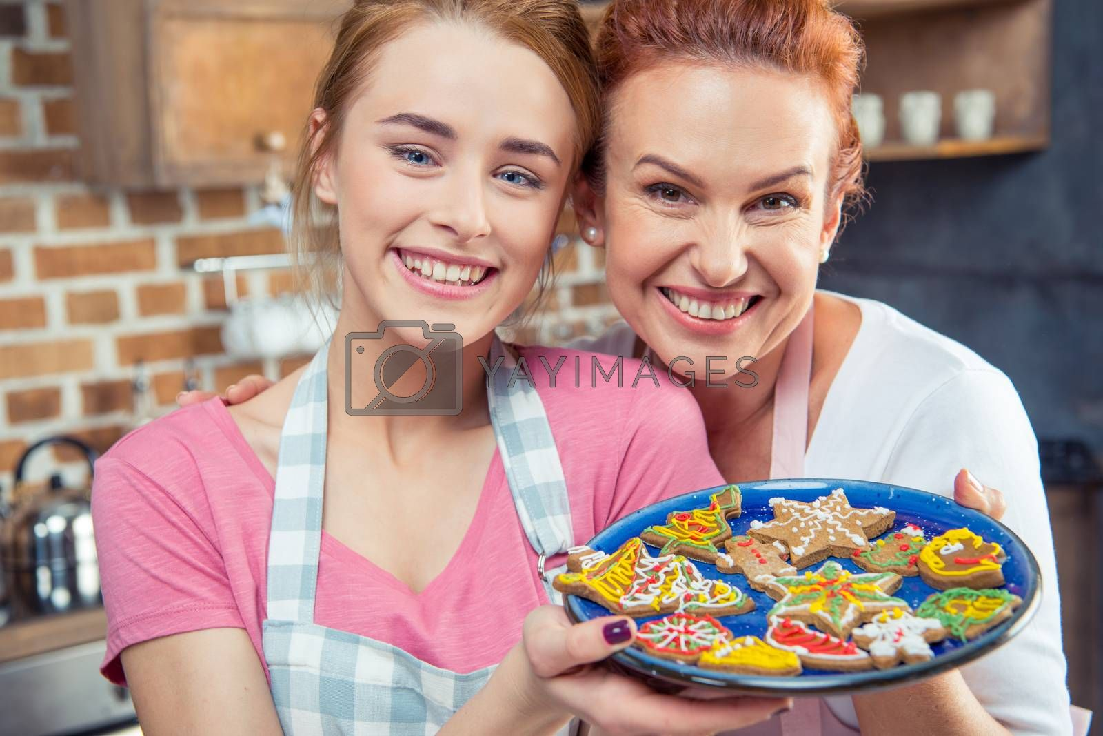 Smiling mother and her daughter holding plate with Christmas cookies and smiling