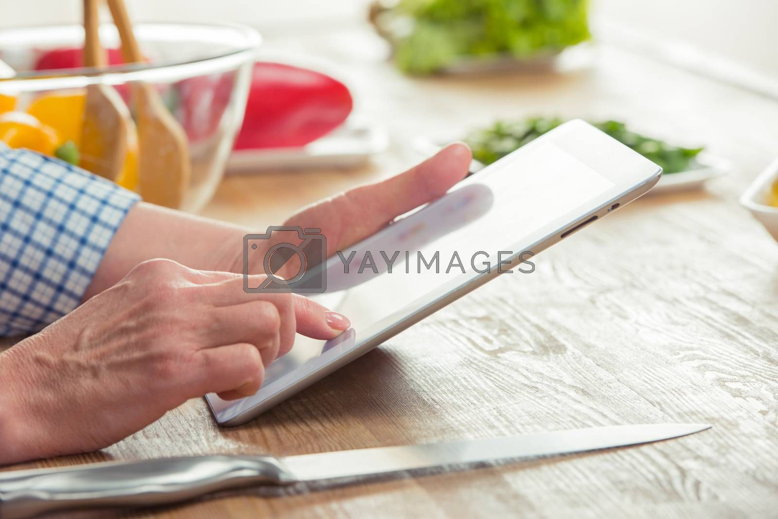 Close-up partial view of woman using digital tablet in kitchen