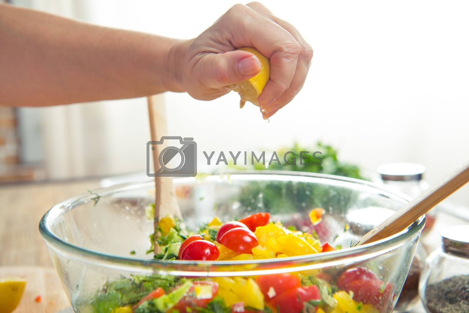 Close-up partial view of woman squeezing lemon in bowl with vegetable salad