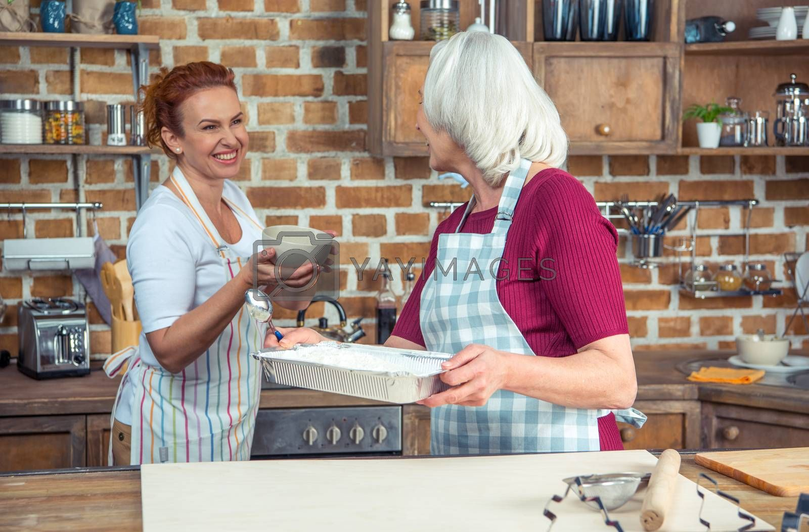 Two women preparing ingredients for baking in kitchen