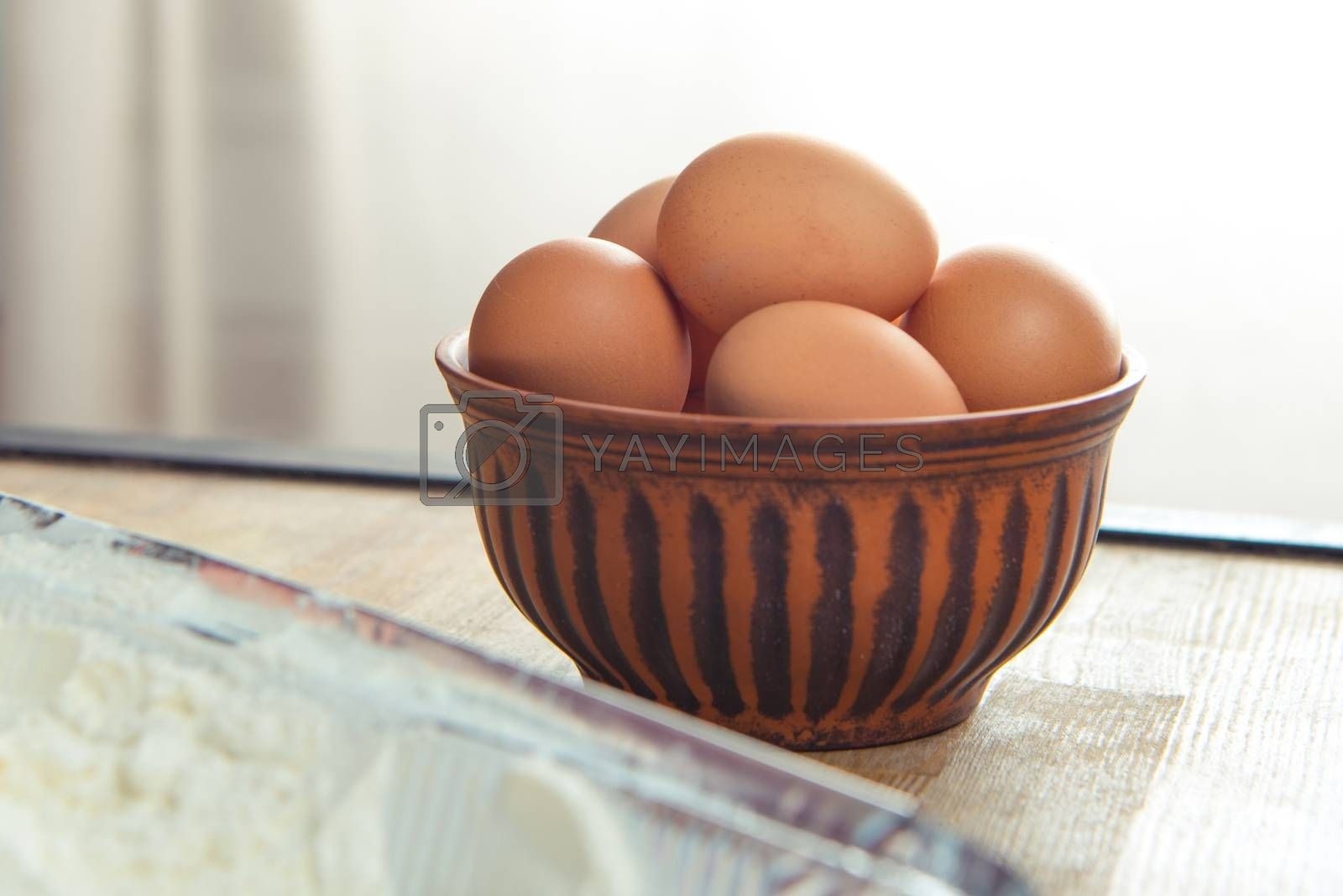 Close-up view of raw eggs in bowl on kitchen table