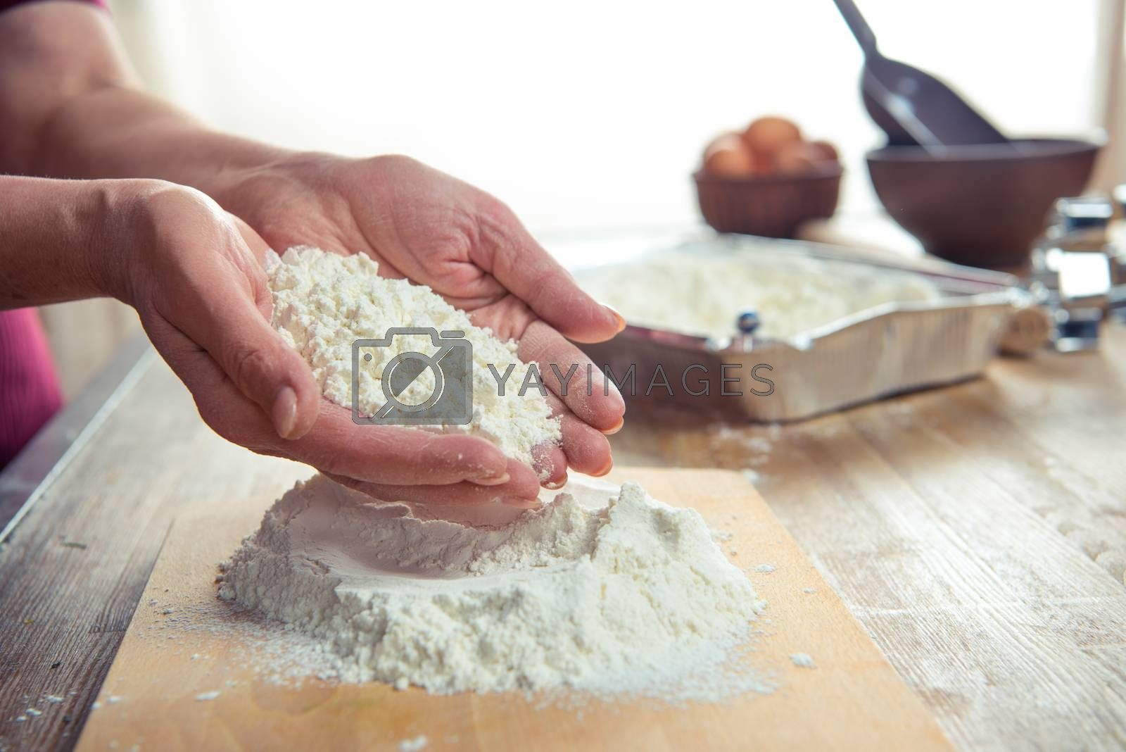Partial view of flour in female hands