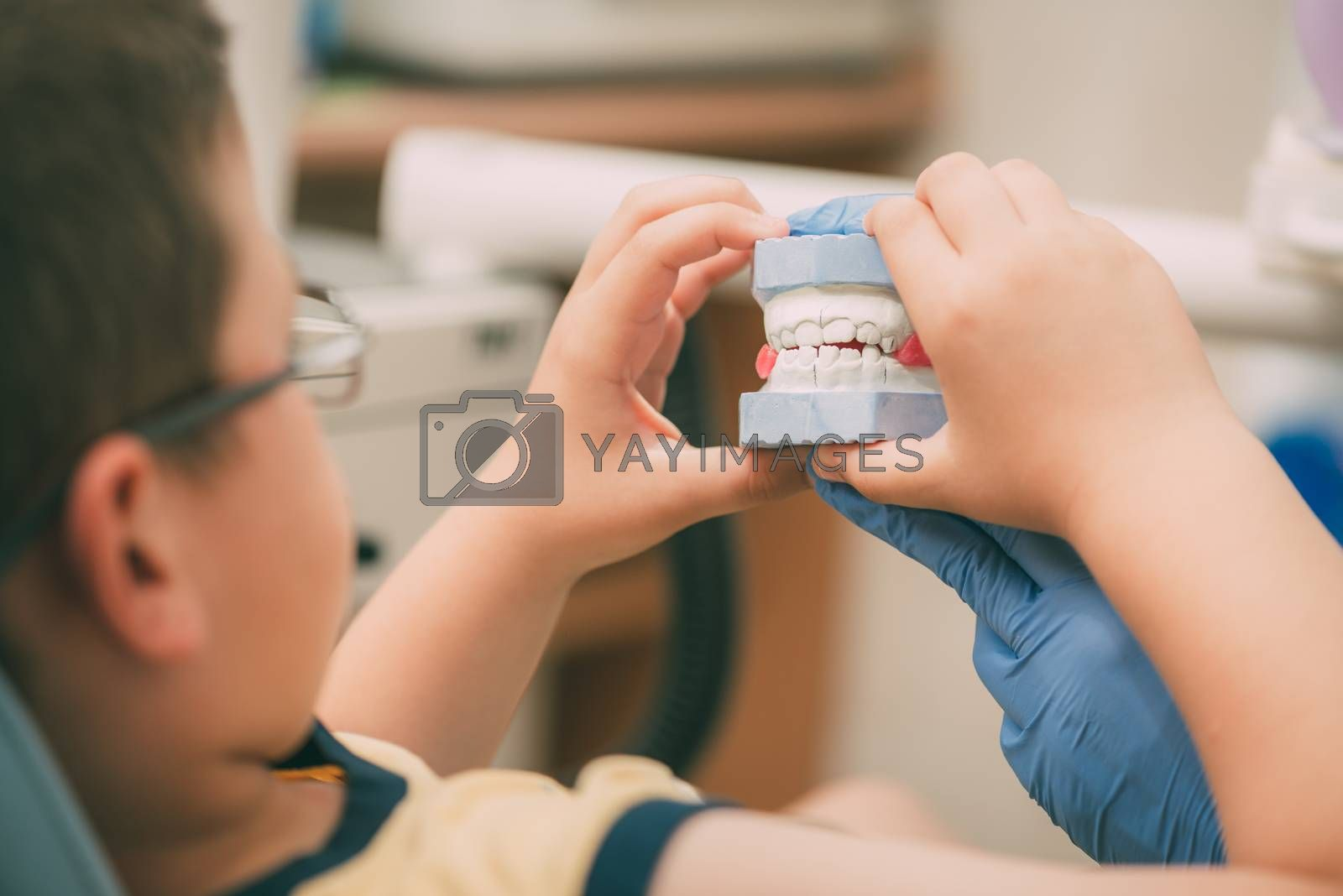 Dentist showing plaster cast jaws to the little boy patient. Selective focus.