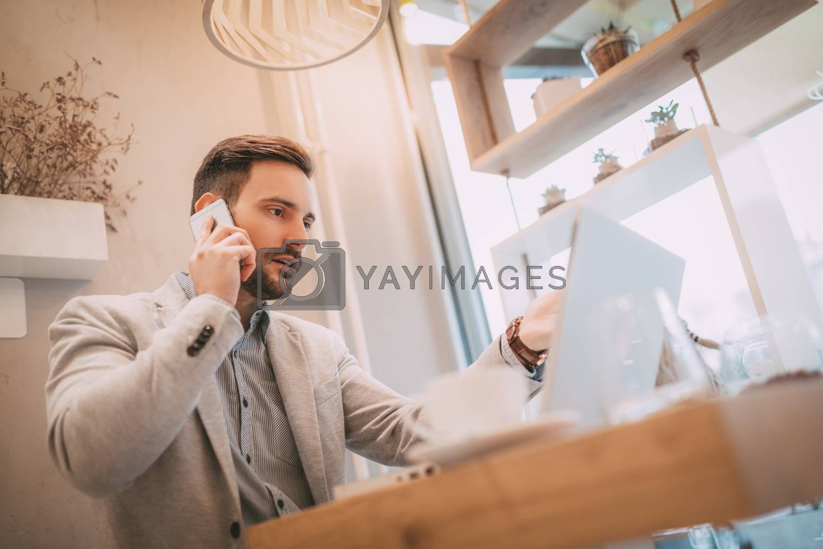 Young businessman on a break in a cafe. He is working at tablet and using smart phone.