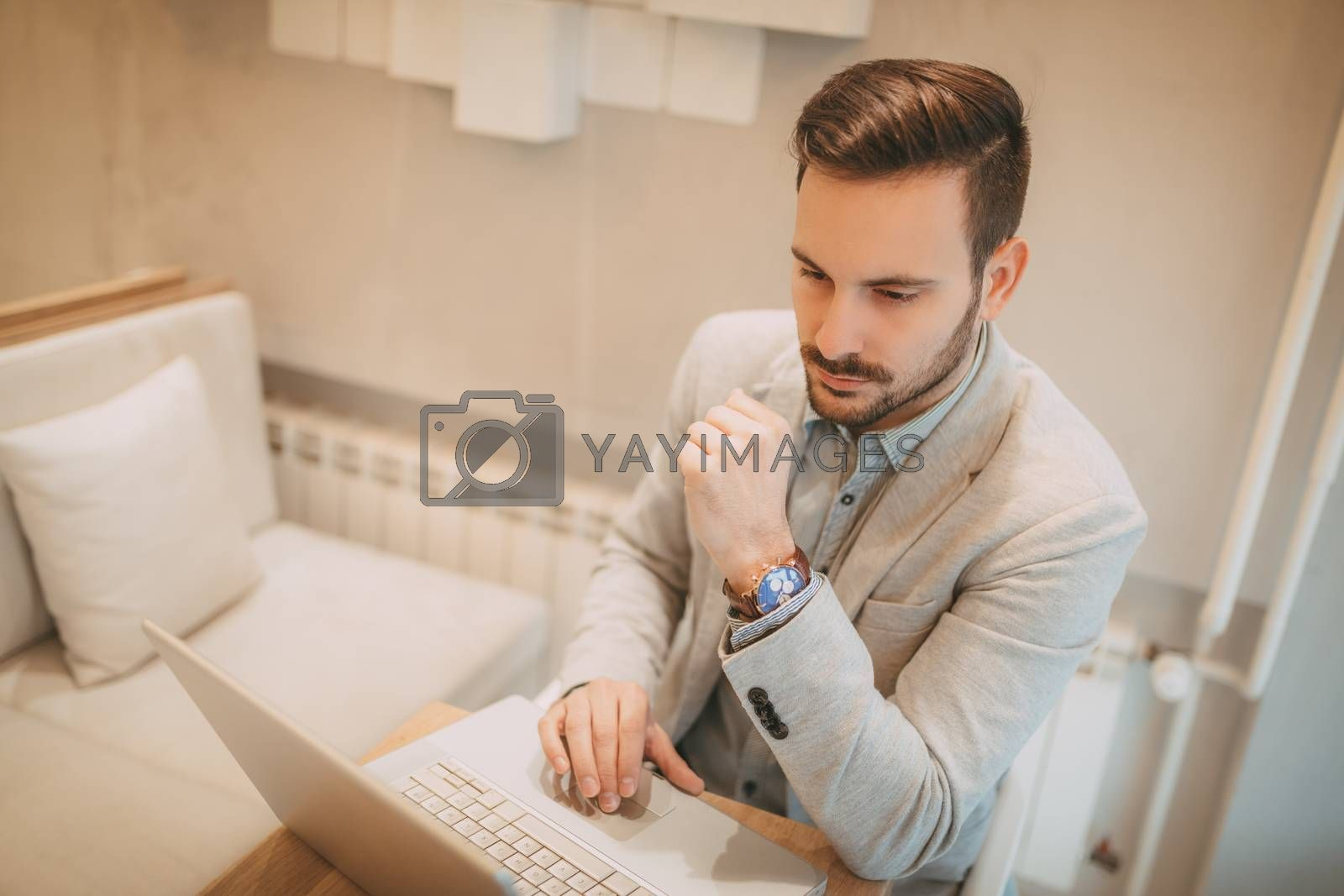 Young pensive businessman on a break in a cafe. He is working at tablet and using smart phone.
