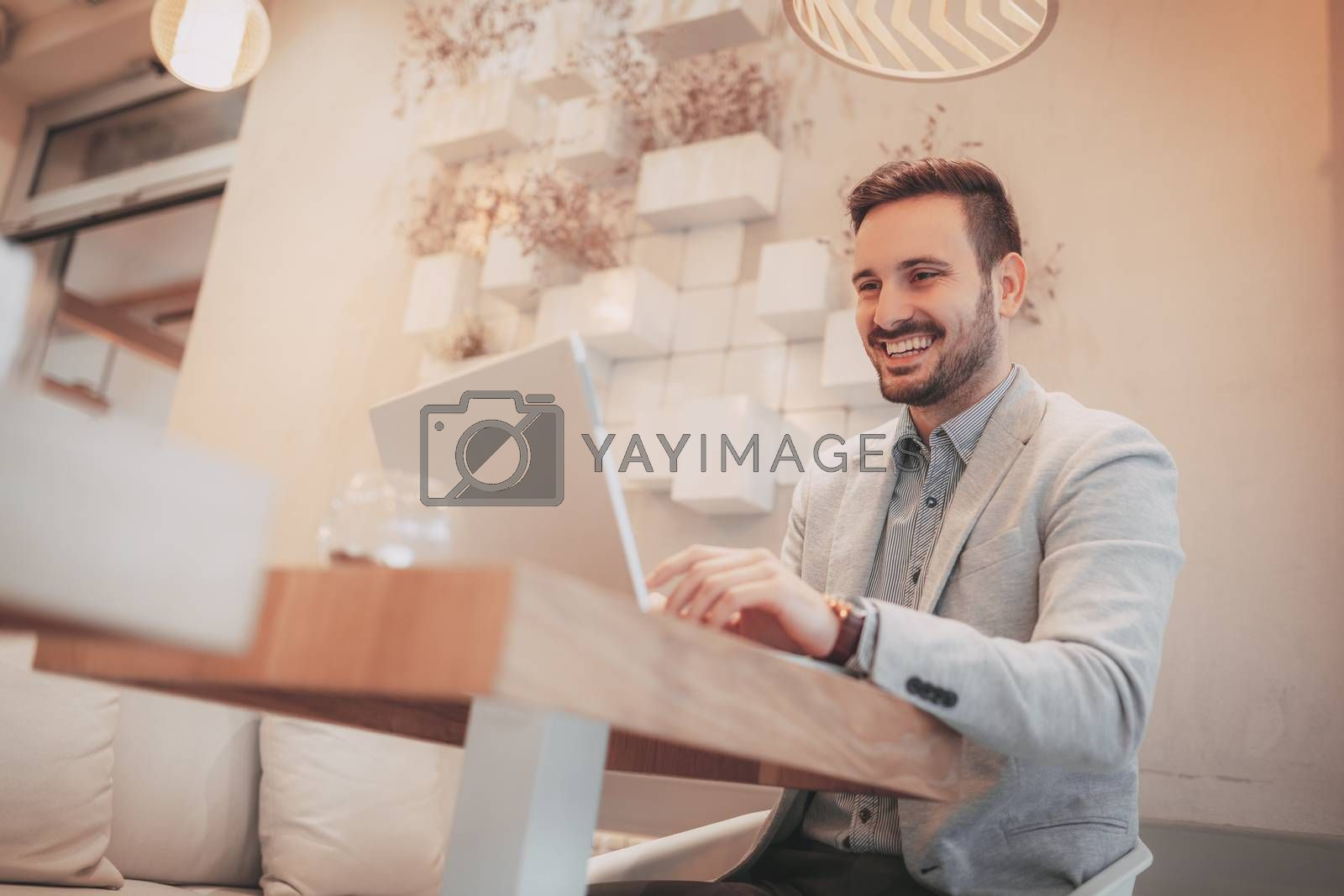 Young smiling businessman on a break in a cafe. He is working at tablet and using smart phone.