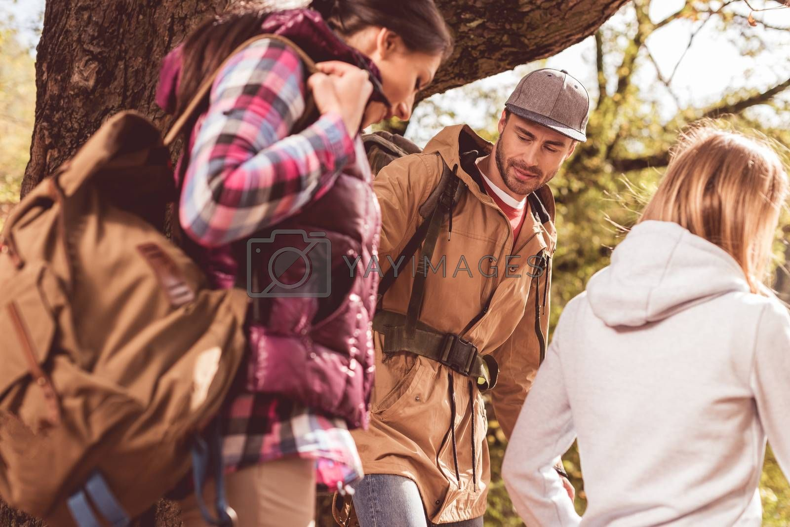 Low angle view of group of young backpackers walking in autumn forest