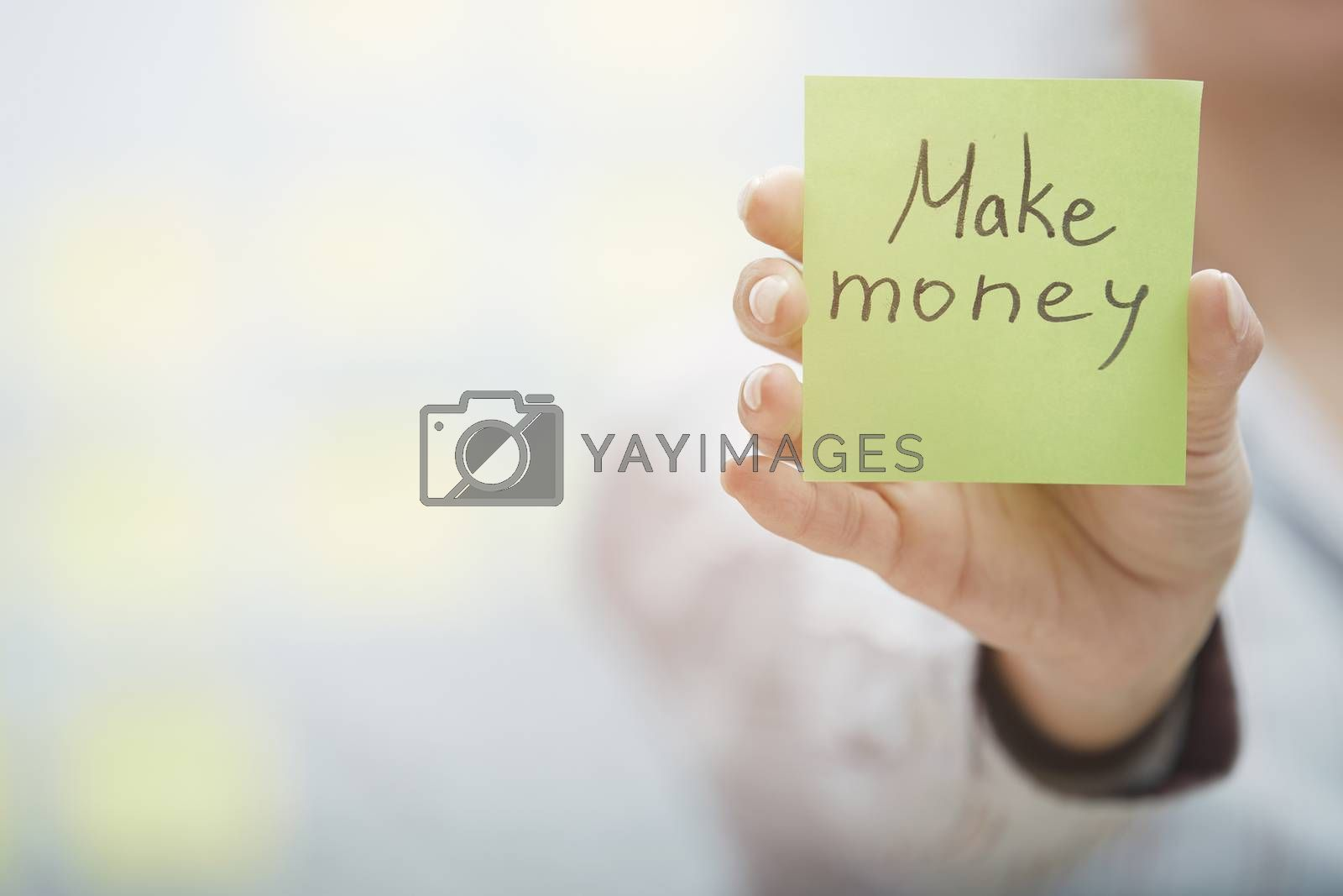 Woman holding sticky note with Make money text