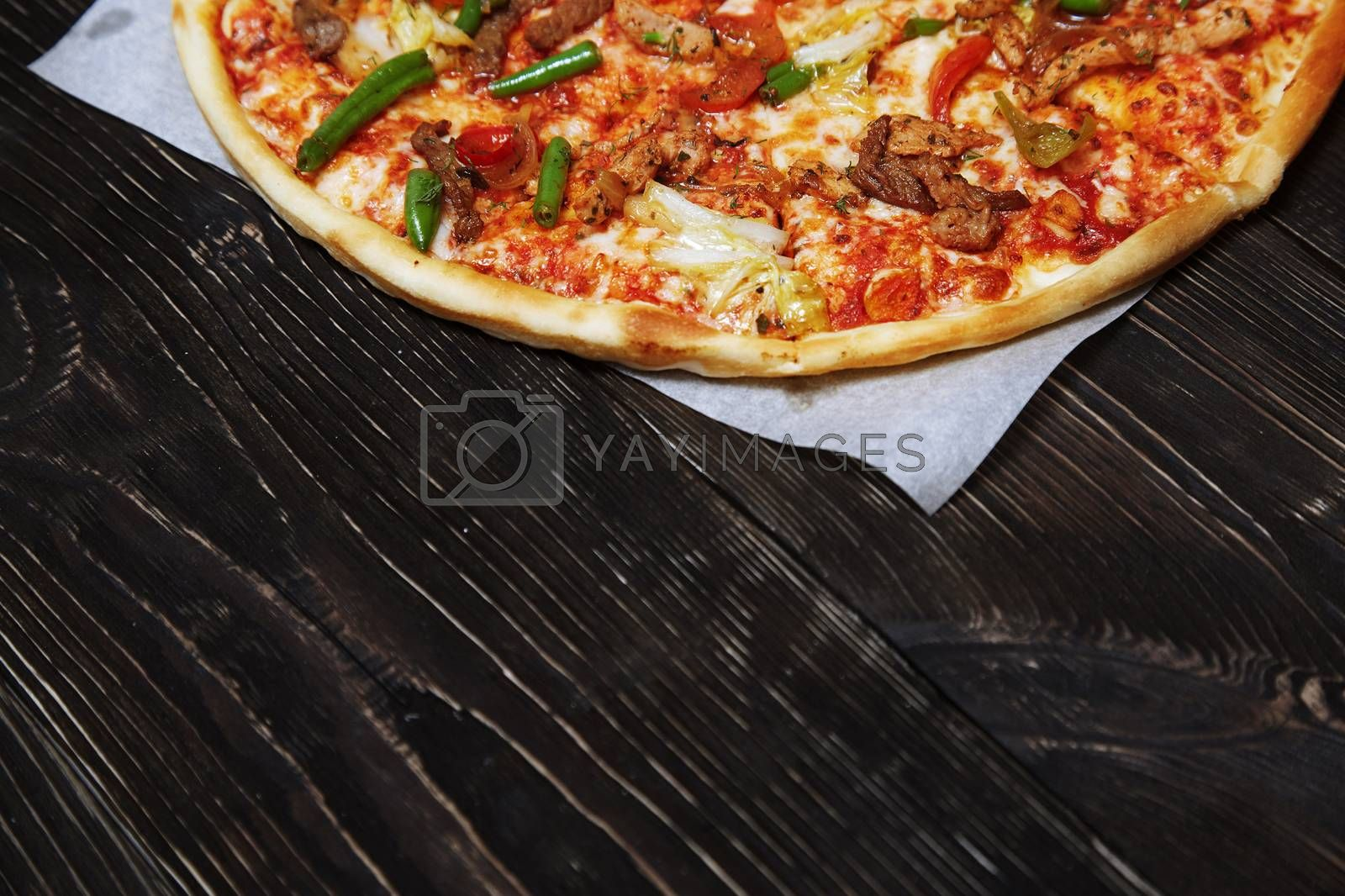 Part of homemade pizza on a wooden table