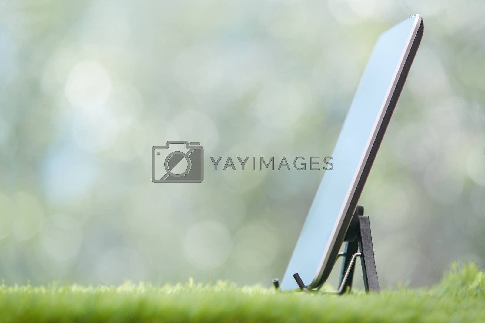 Digital tablet on a lawn. Horizontal photo