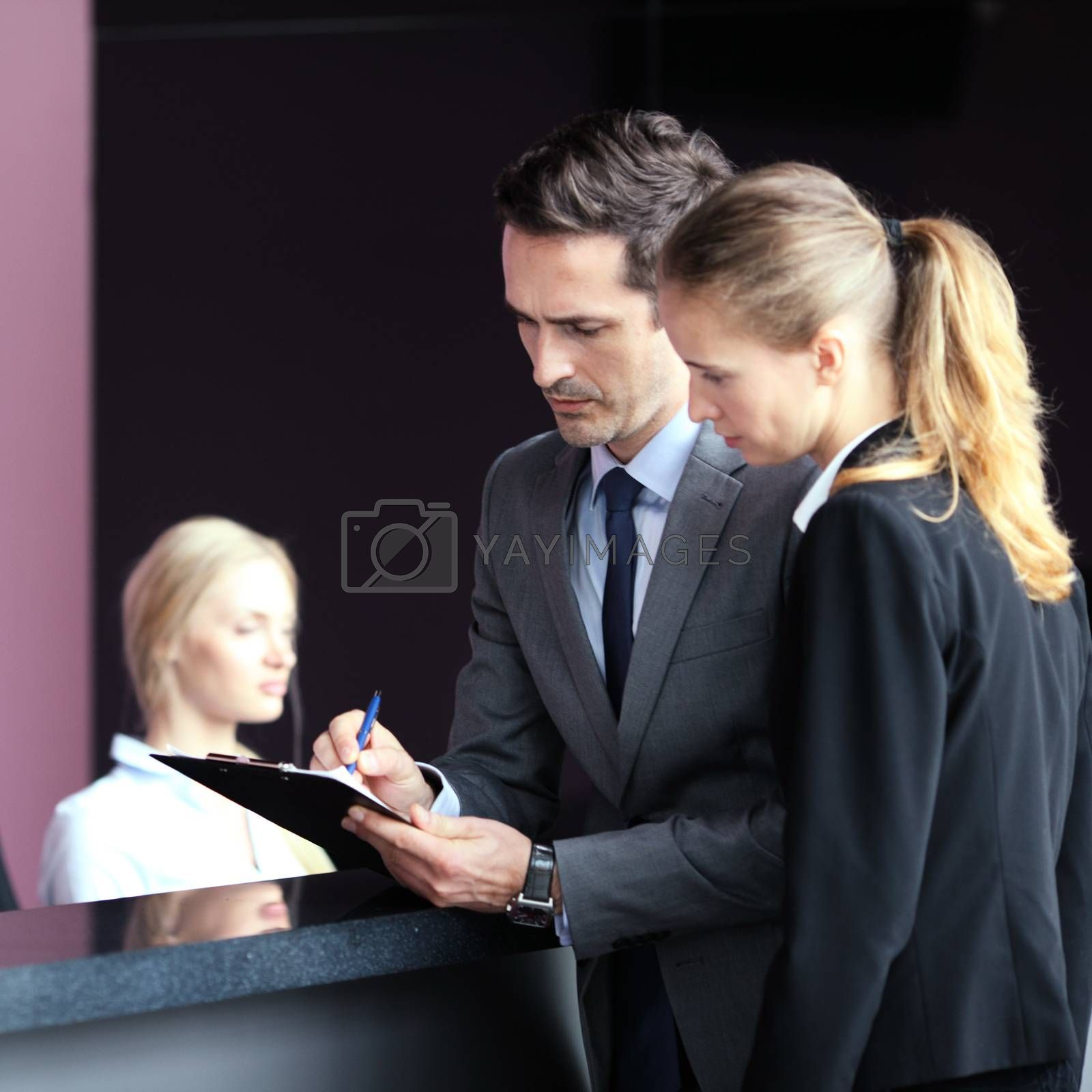 Business people filling forms at reception front desk