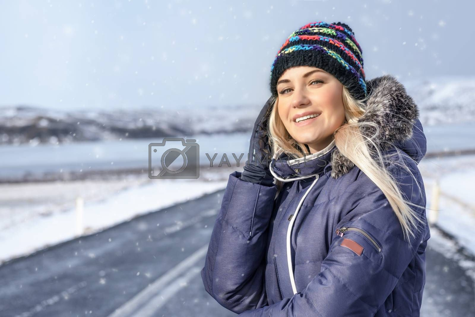 Young people traveling in winter, portrait of a beautiful smiling girl enjoying road trip, standing on the road in snowy wintertime day, tourist in Iceland