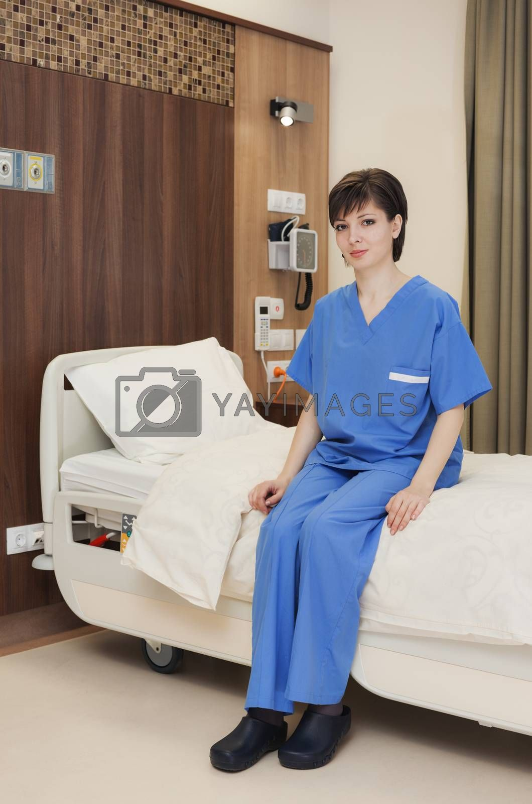A young female patient sitting on medical bed in modern hospital room.